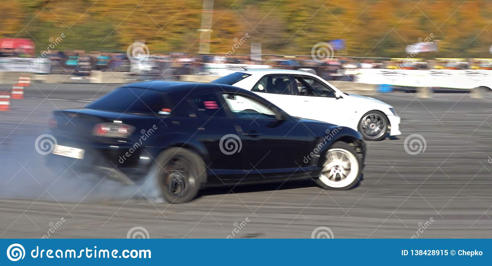 Un coche de competición de la deriva en la acción con los neumáticos que fuman en la demostración