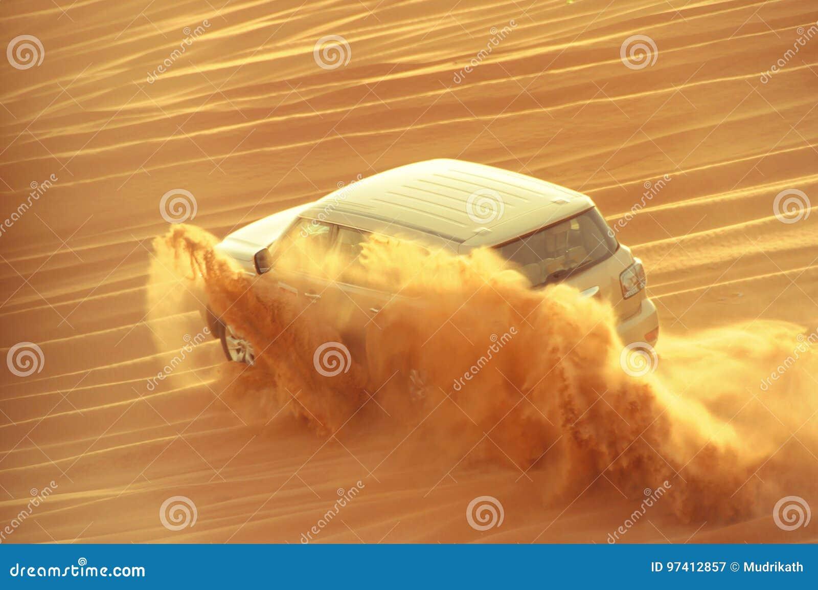 Un coche de cuatro ruedas de la impulsión en la acción en un viaje del safari del desierto en los Dubai-UAE el 21 de julio de 201