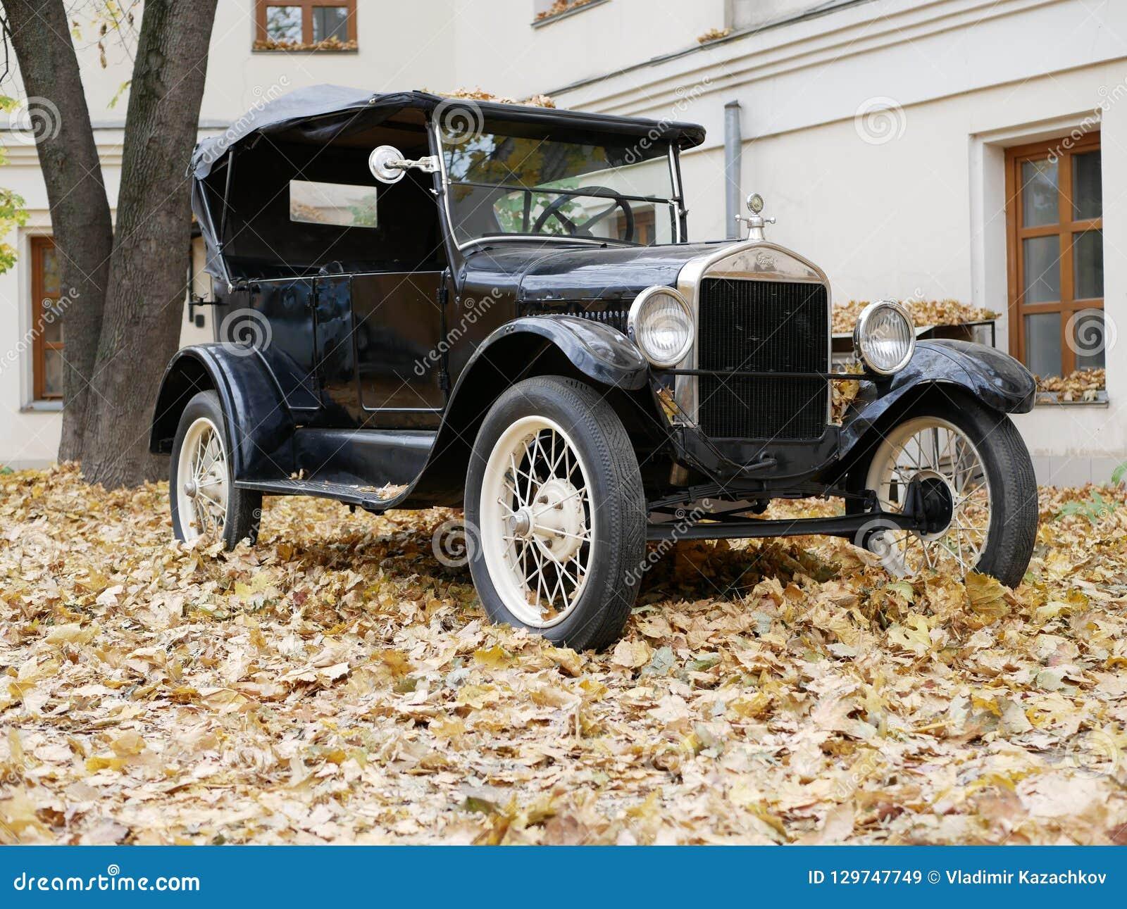 Un coche viejo en la yarda que se cubre con las hojas de arce amarillas