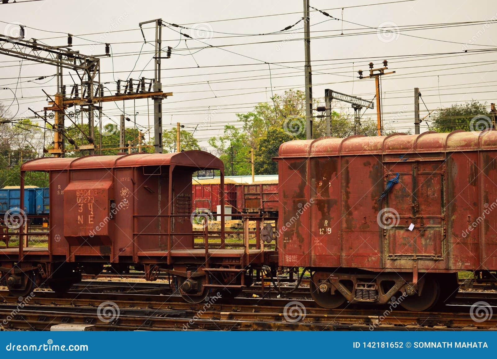 Un compartimento indiano colorato arrugginito delle guardie del treno merci legato con il treno merci
