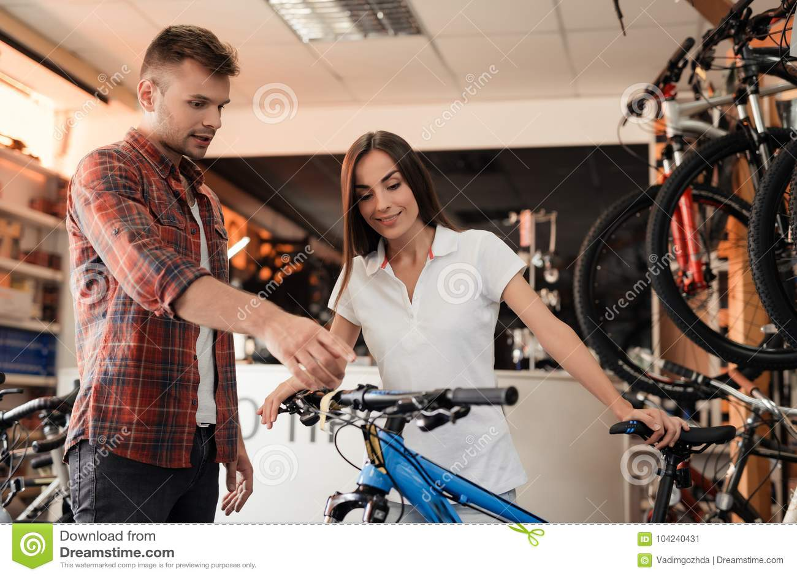 Un consulente in materia della ragazza mostra il compratore in un negozio di biciclette