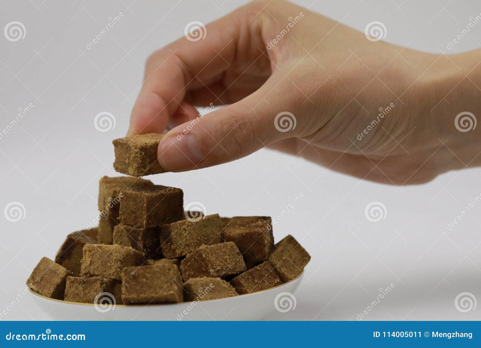 Un control de la mano de la mujer al pedazo de azúcar marrón, cubos oscila el azúcar en una placa, en el fondo blanco, diabetes