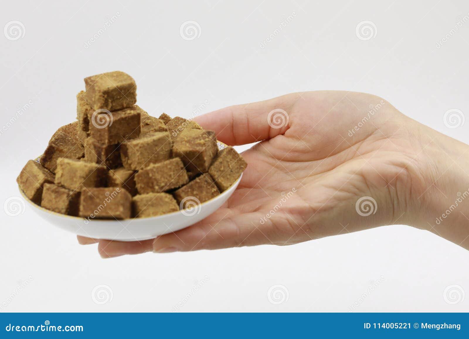 Un control de la mano de la mujer una placa del azúcar marrón, cubos oscila el azúcar en una placa, en el fondo blanco, diabetes