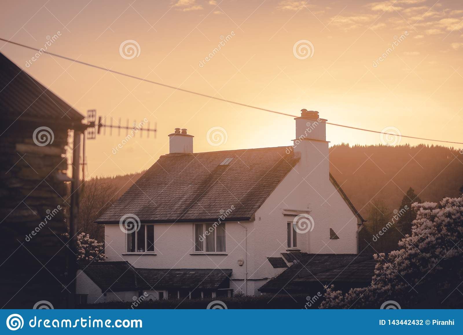 Un cottage anglais couvert de chaume confortable avec le soleil orange chaud plaçant derrière lui au milieu du ressort
