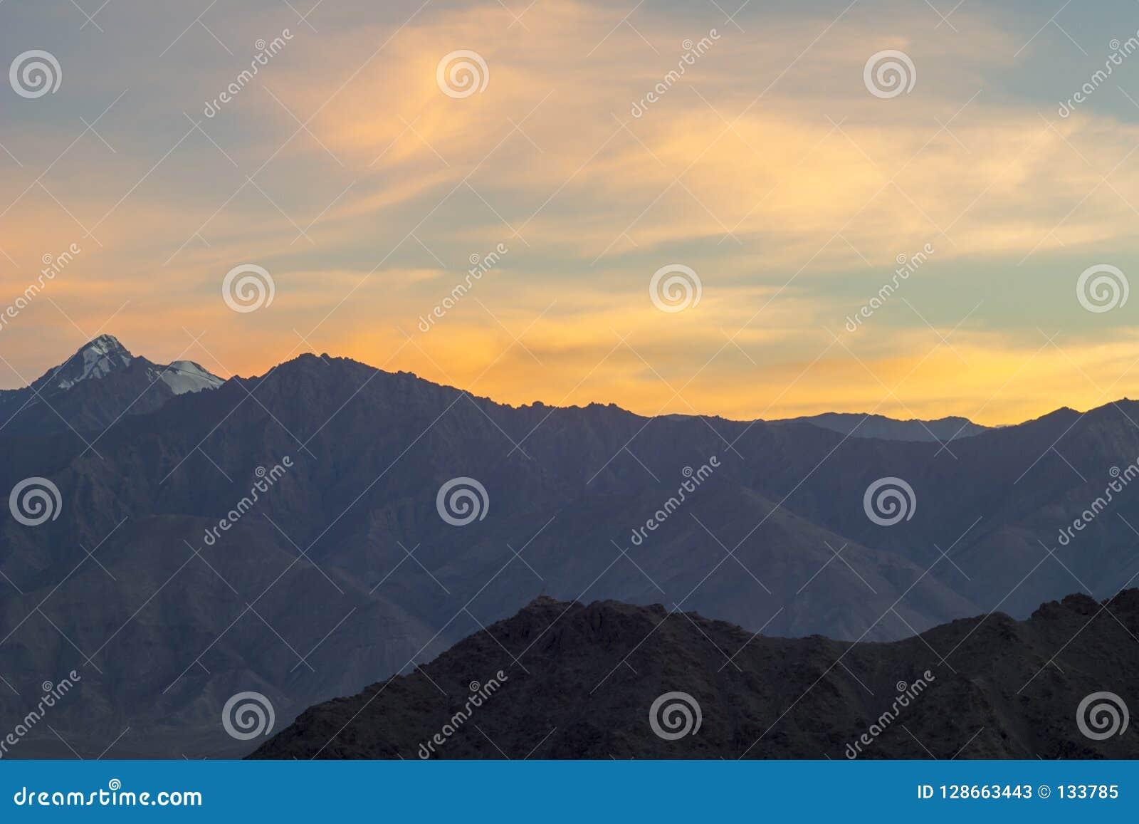 Un coucher du soleil orange rose d or au-dessus de la vallée de montagnes