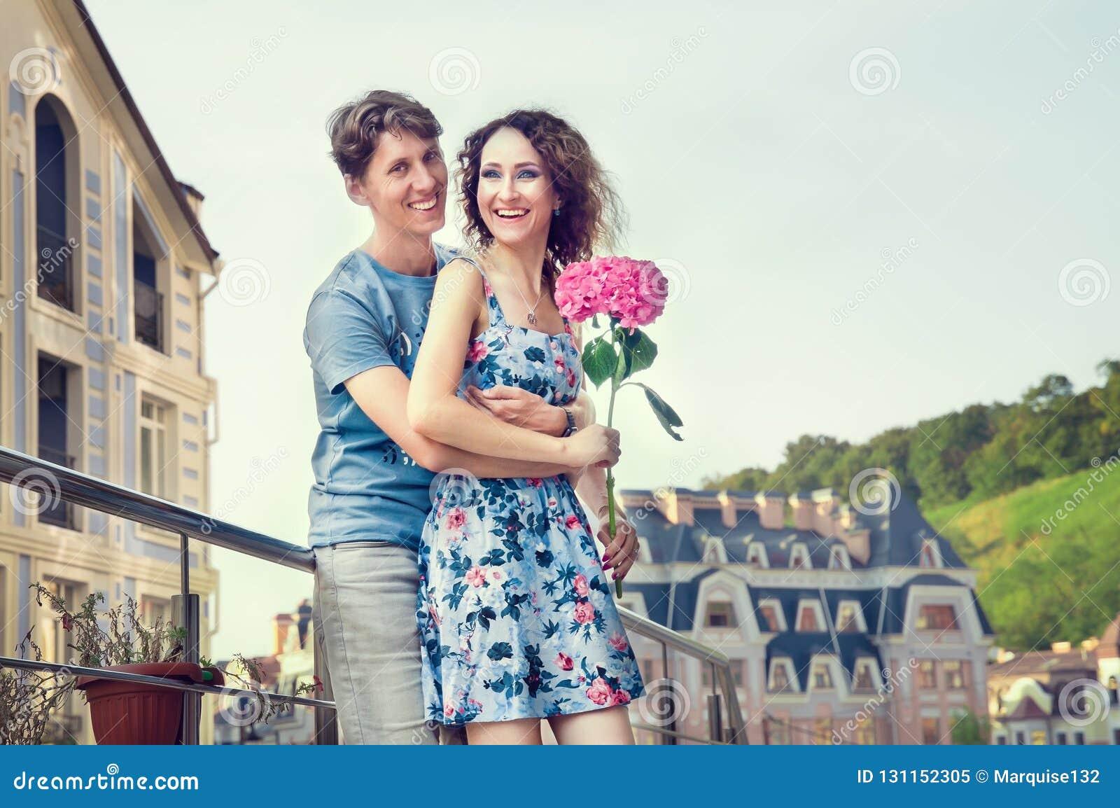 Un couple affectueux est embrassant et riant heureusement dans la perspective d une vieille rue et d un ciel clair La fille dans