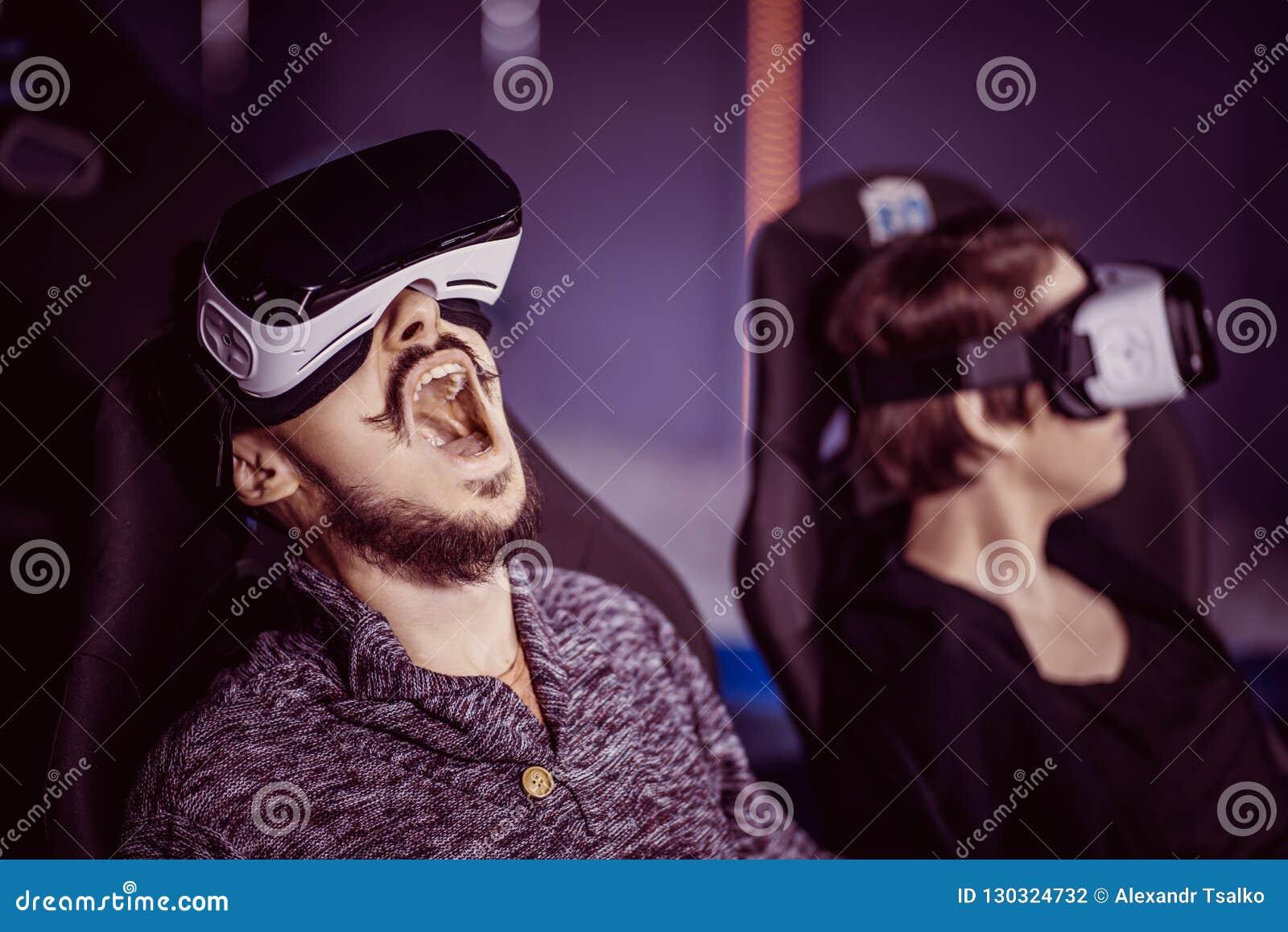 Un couple ayant l amusement au cinéma en verres virtuels avec le specia