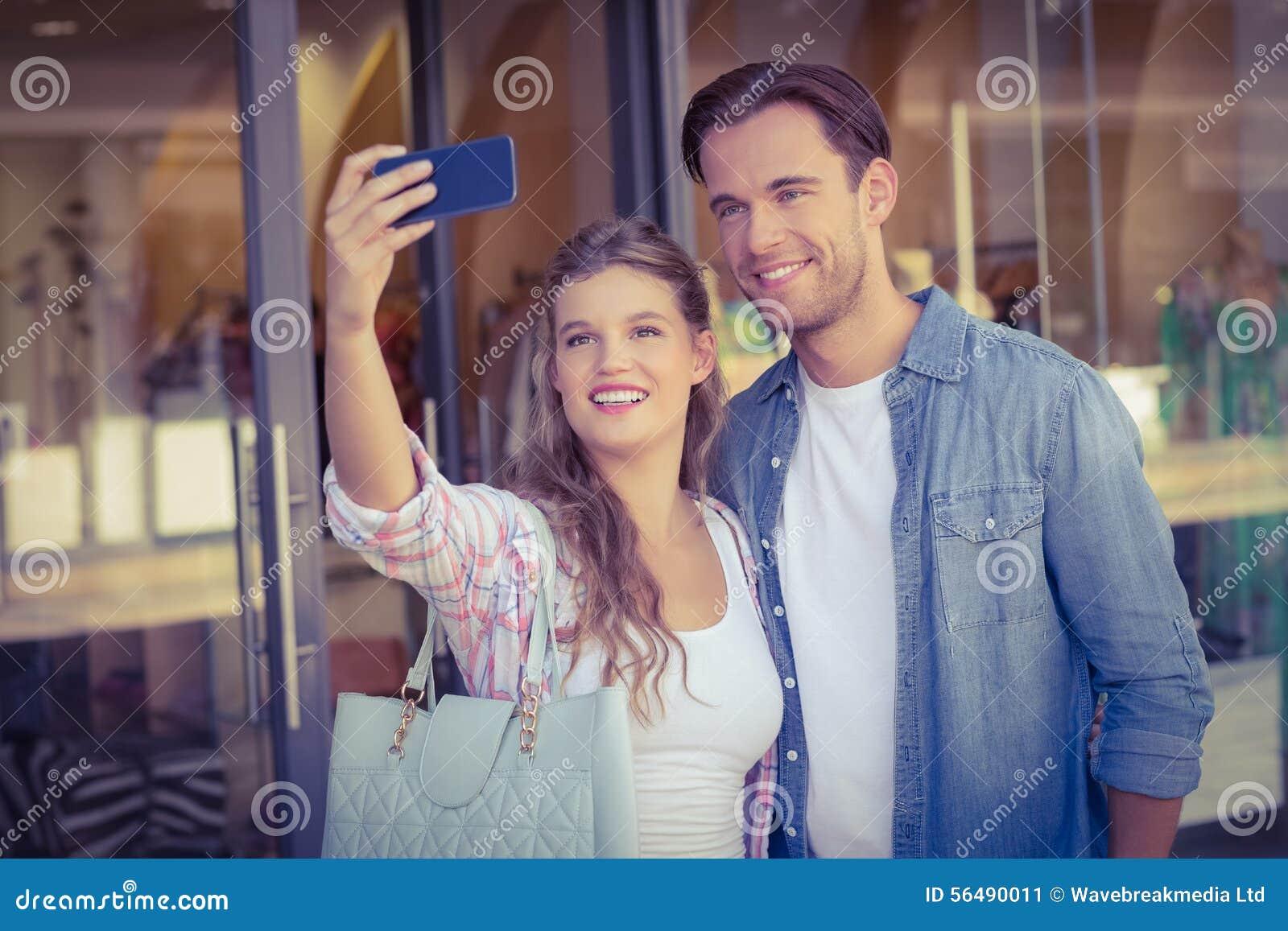 Un couple heureux de sourire prenant des selfies