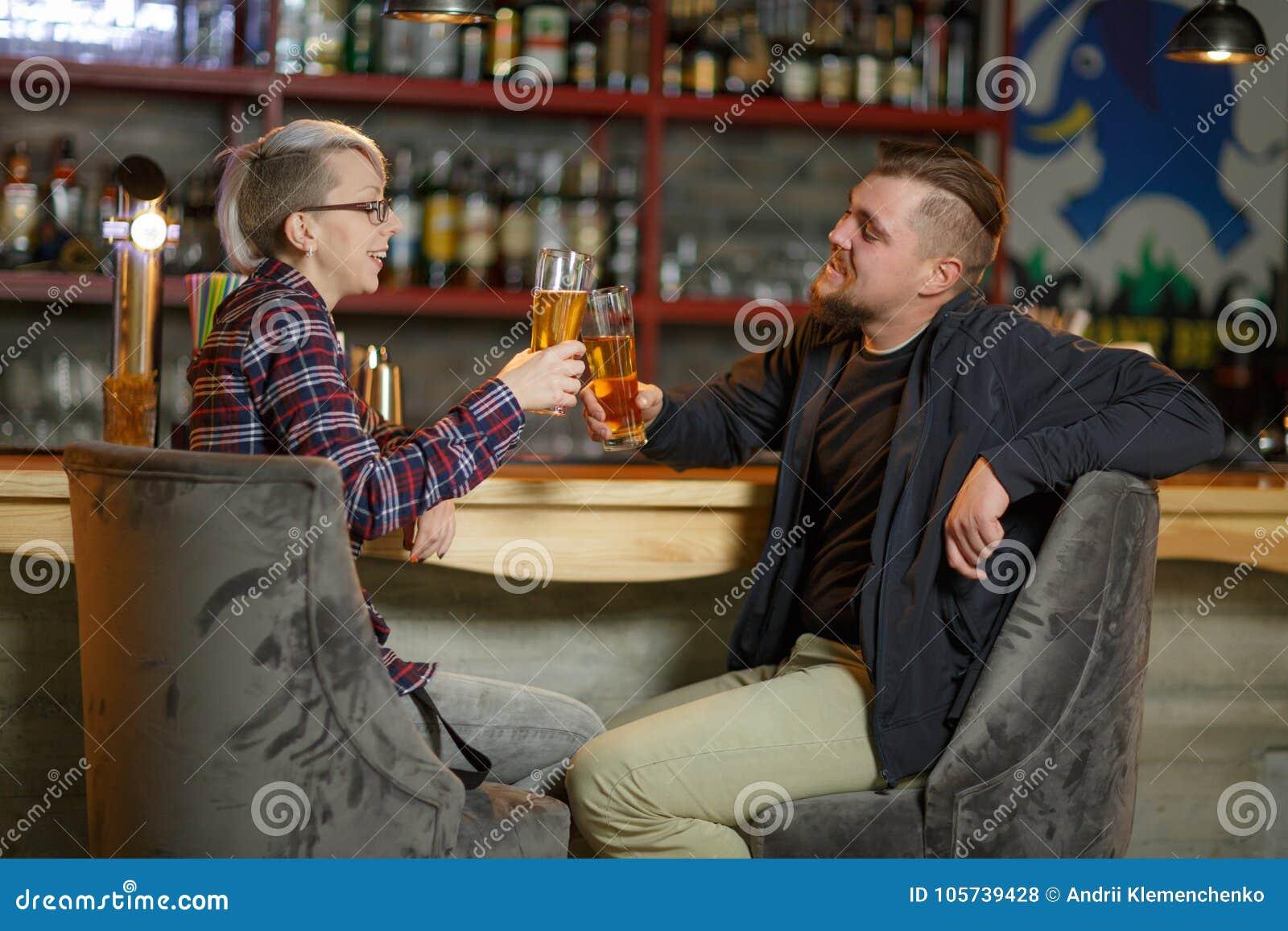 Un couple se reposant dans une barre, une causerie et des acclamations avec des verres de bière indoors