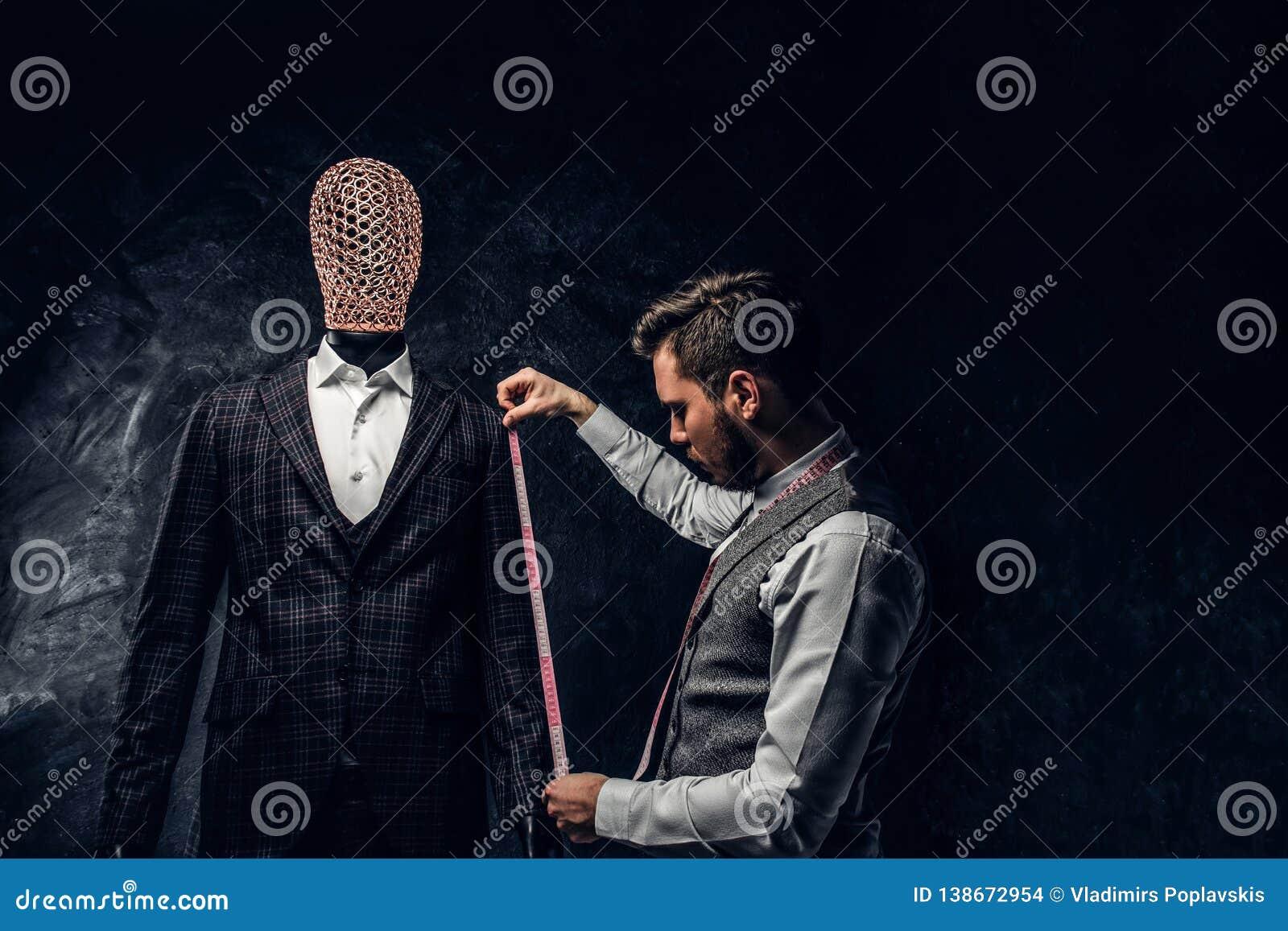 Un couturier avec une bande de mesure vérifier la longueur des douilles d un costume d hommes élégants faits sur commande dans un