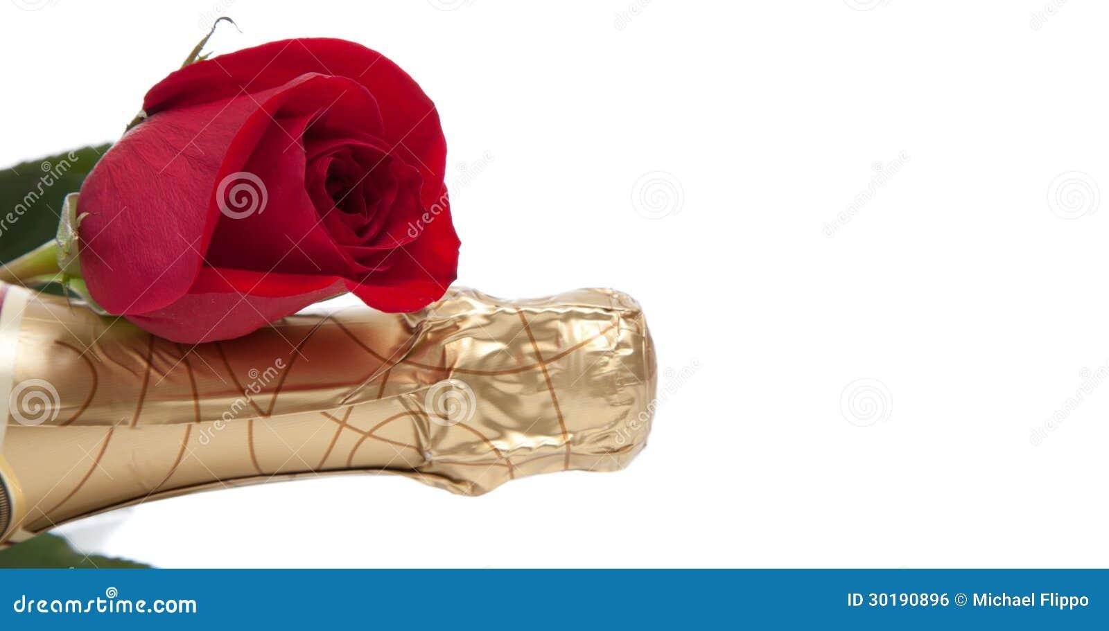 El cuello de una botella del champán con una rosa roja en blanco