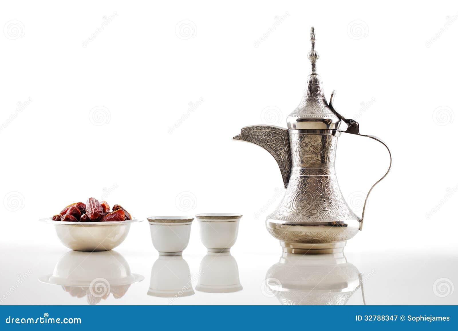 Un dallah, un vaso del metallo per produrre caffè arabo con una ciotola di datteri secchi