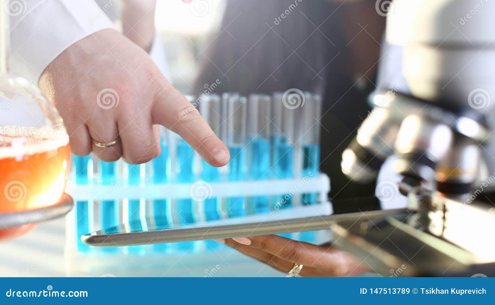 Un doctor de sexo femenino en un laboratorio de la sustancia qu?mica se sostiene