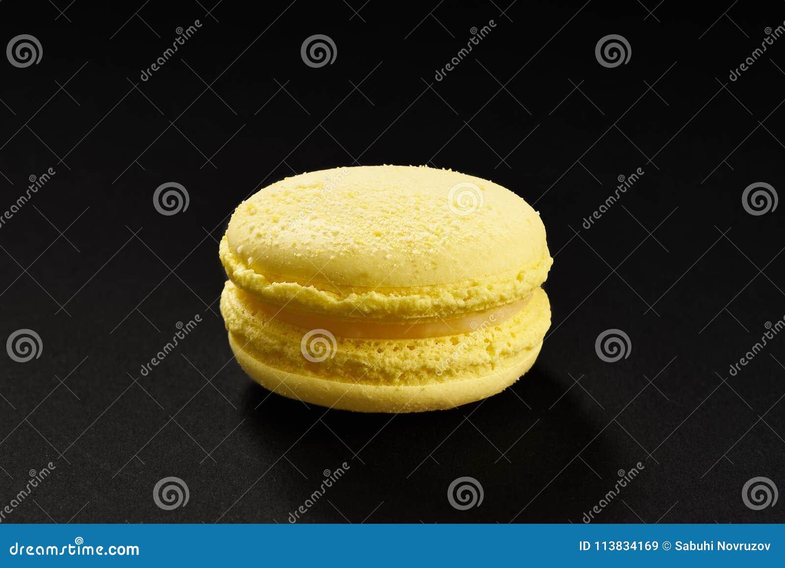 Un dolce di colore del limone di giallo dei maccheroni Maccherone delizioso isolato su fondo nero Biscotto dolce francese