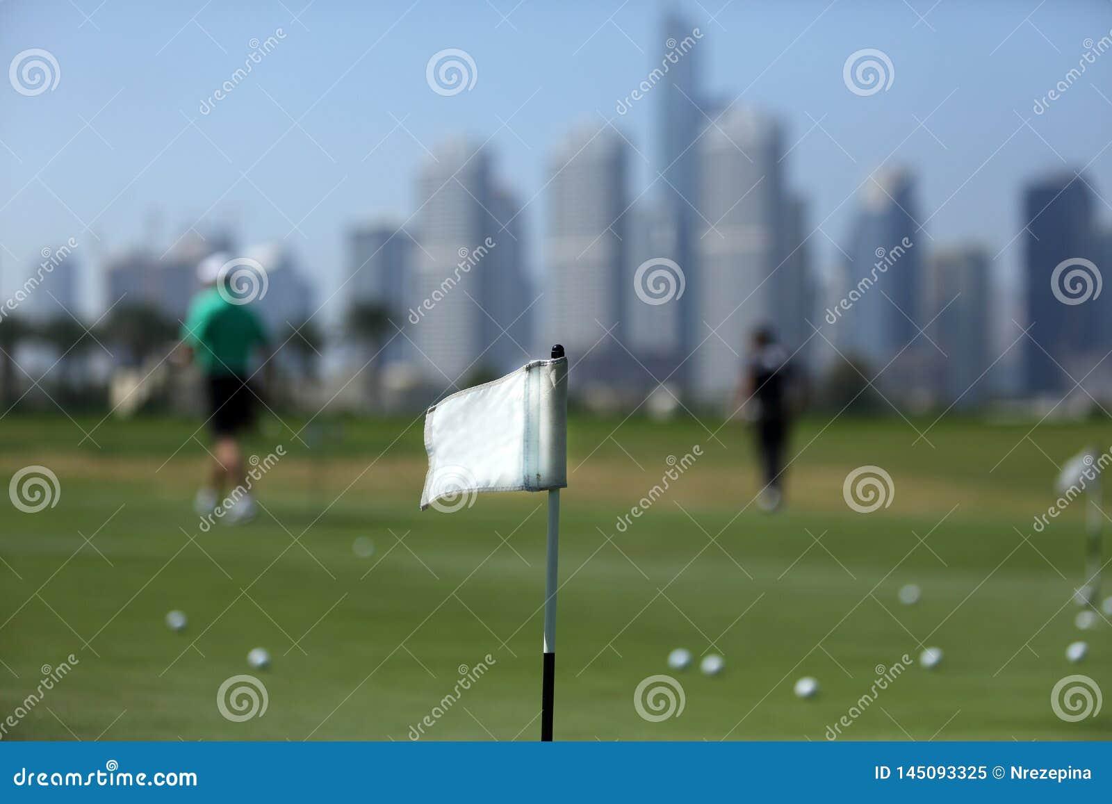 Un drapeau sur le terrain de golf parmi des golfeurs et des gratte-ciel au Dubaï