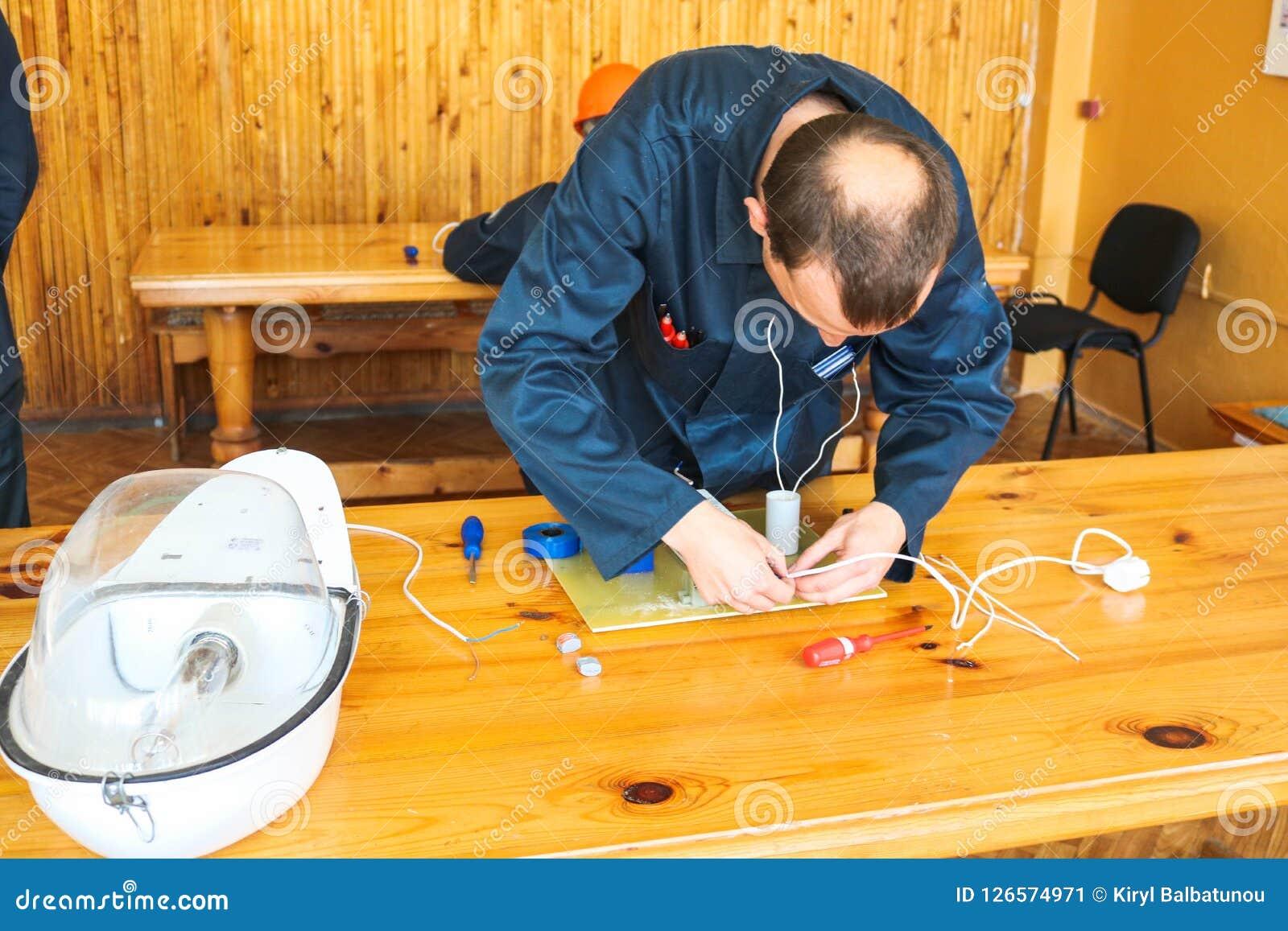 Un elettricista dell uomo che lavora gli impianti, raccoglie il circuito elettrico di grande lampada di via bianca con i cavi, un