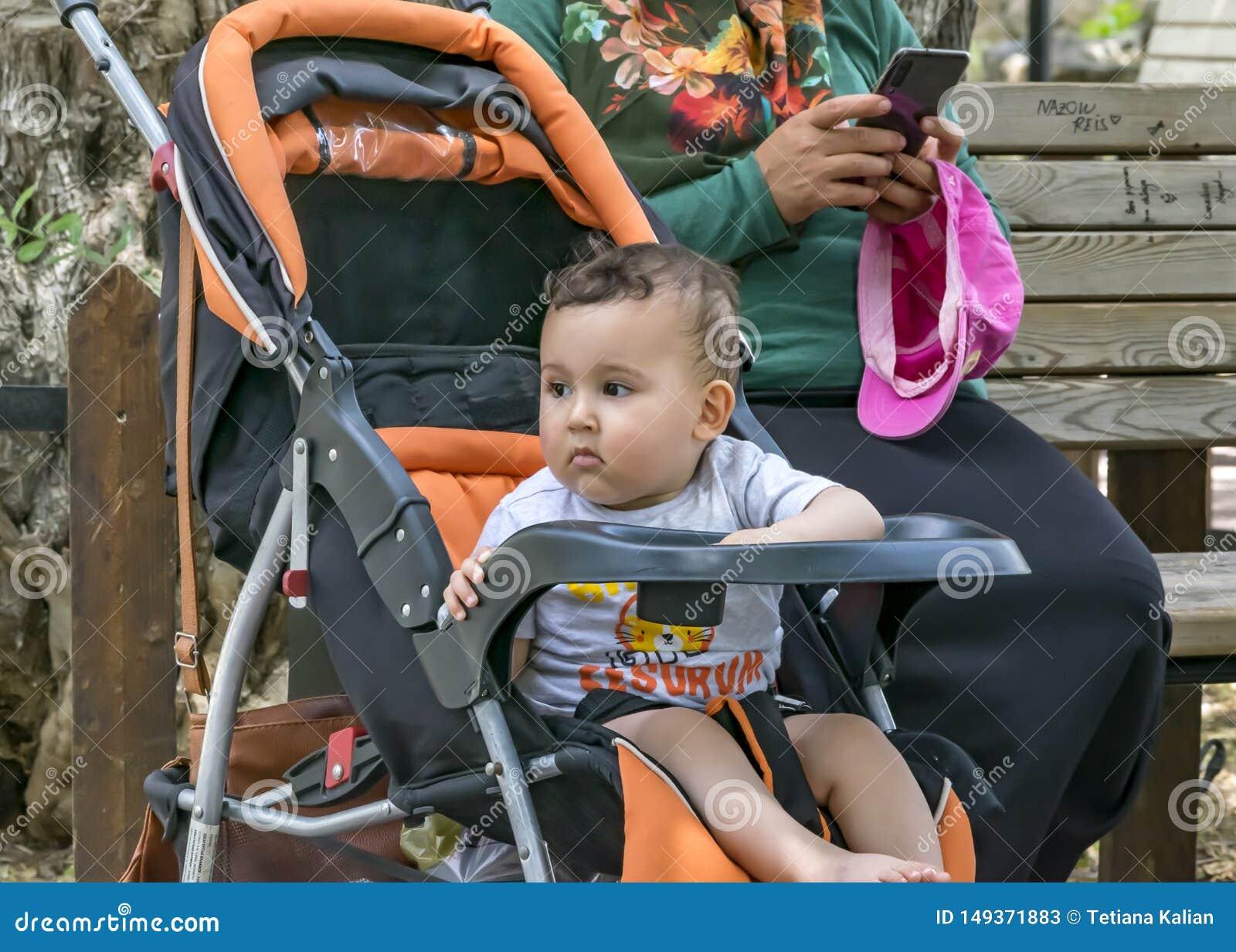 Un enfant a ennuyé la séance dans une poussette de bébé Une mère féminine habillée dans l habillement musulman traditionnel utili