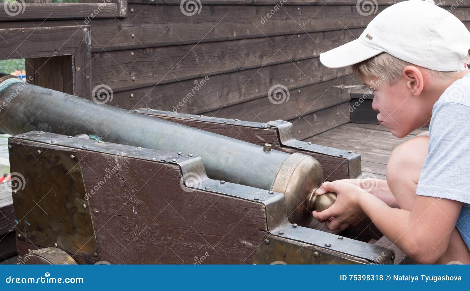 Un enfant jouant avec une vieille arme à feu sur le bateau