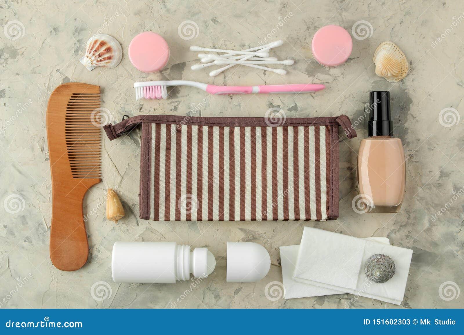 Un ensemble de cosmétiques et de produits de soin personnel pour le voyage dans un sac cosmétique sur un fond de ciment Vue sup?r