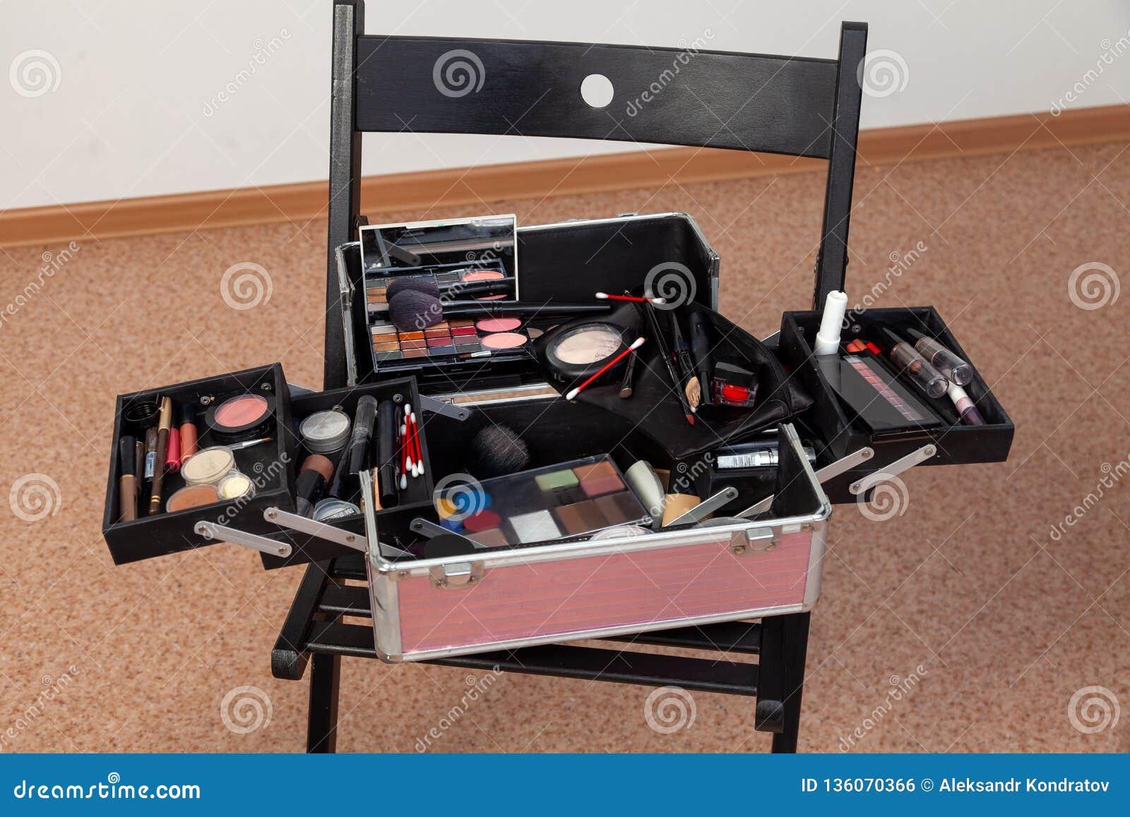 Un ensemble de cosmétiques professionnels dans une boîte de valise sous une forme ouverte sur une chaise dans un studio de beauté