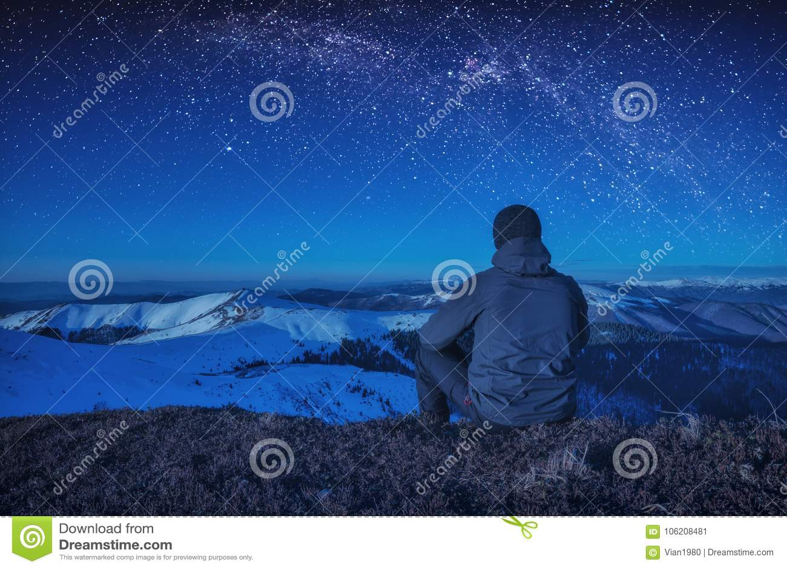 Un escalador que se sienta en una tierra en la noche