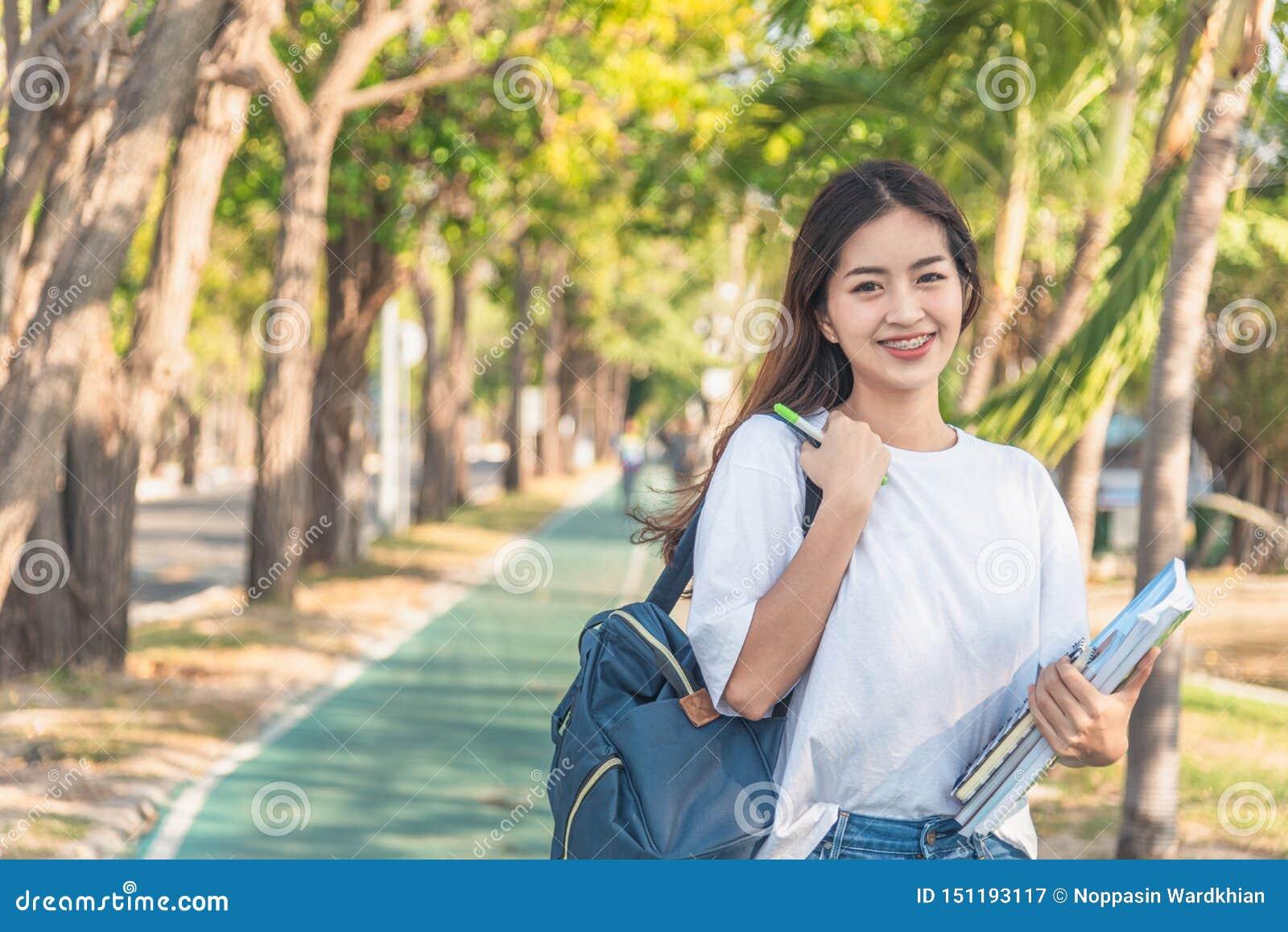 Un estudiante universitario de sexo femenino que lee un libro mientras que miente en el parque