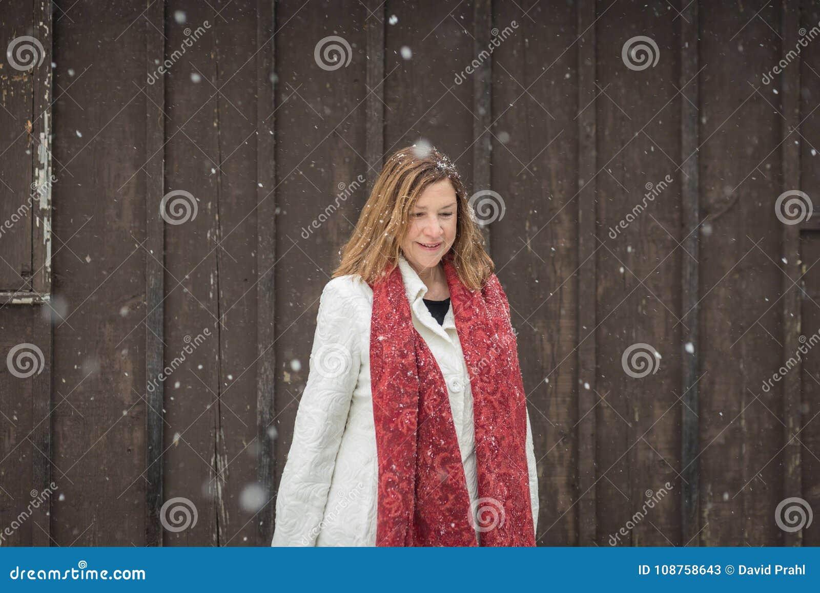 Un exterior derecho de la mujer por el apartadero de madera del granero marrón como luz la Florida