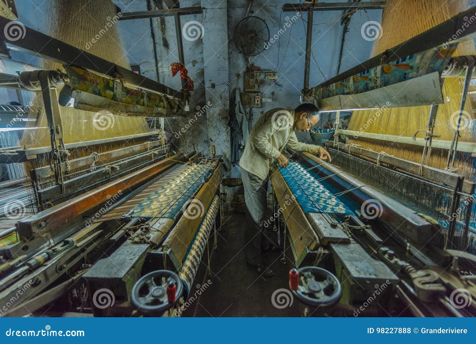 Un fabricante de seda examina su trabajo en una pequeña fábrica en Varanasi, la India