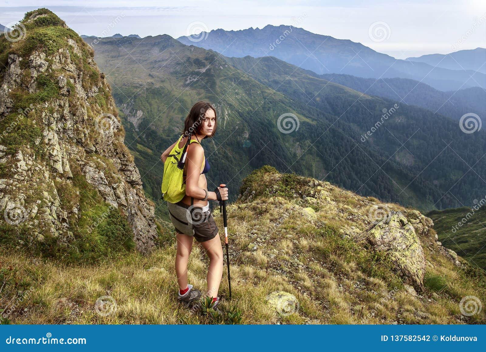 _un fatiguer, torturer femme - un touriste avec un marcher sac à dos regarder avec haine at le photographe qui mener la sur un di