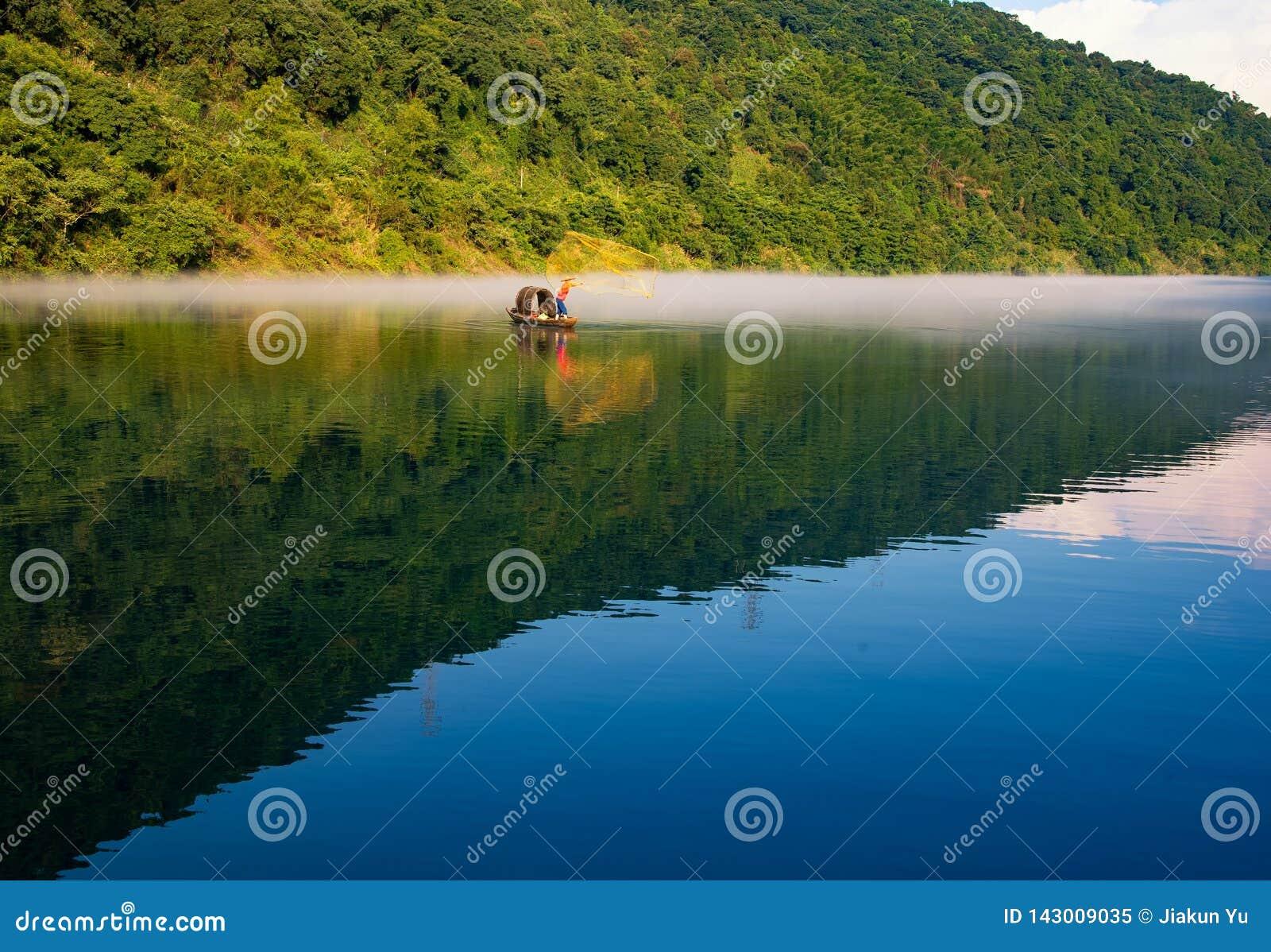 Un fishman echó una red en el barco en la niebla en el río, la reflexión de oro del brillo del sol en la superficie del agua