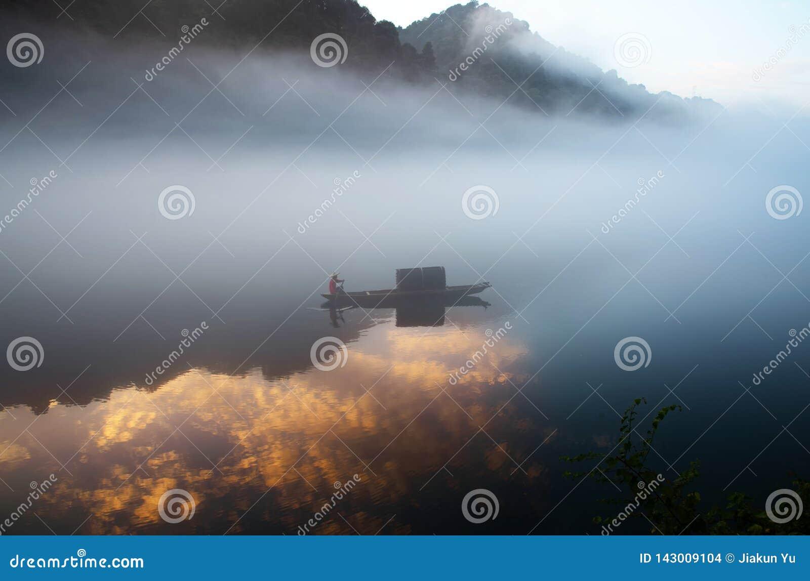 Un fishman en el barco en la niebla en el río, la reflexión de oro de la nube en la superficie del agua, en el amanecer