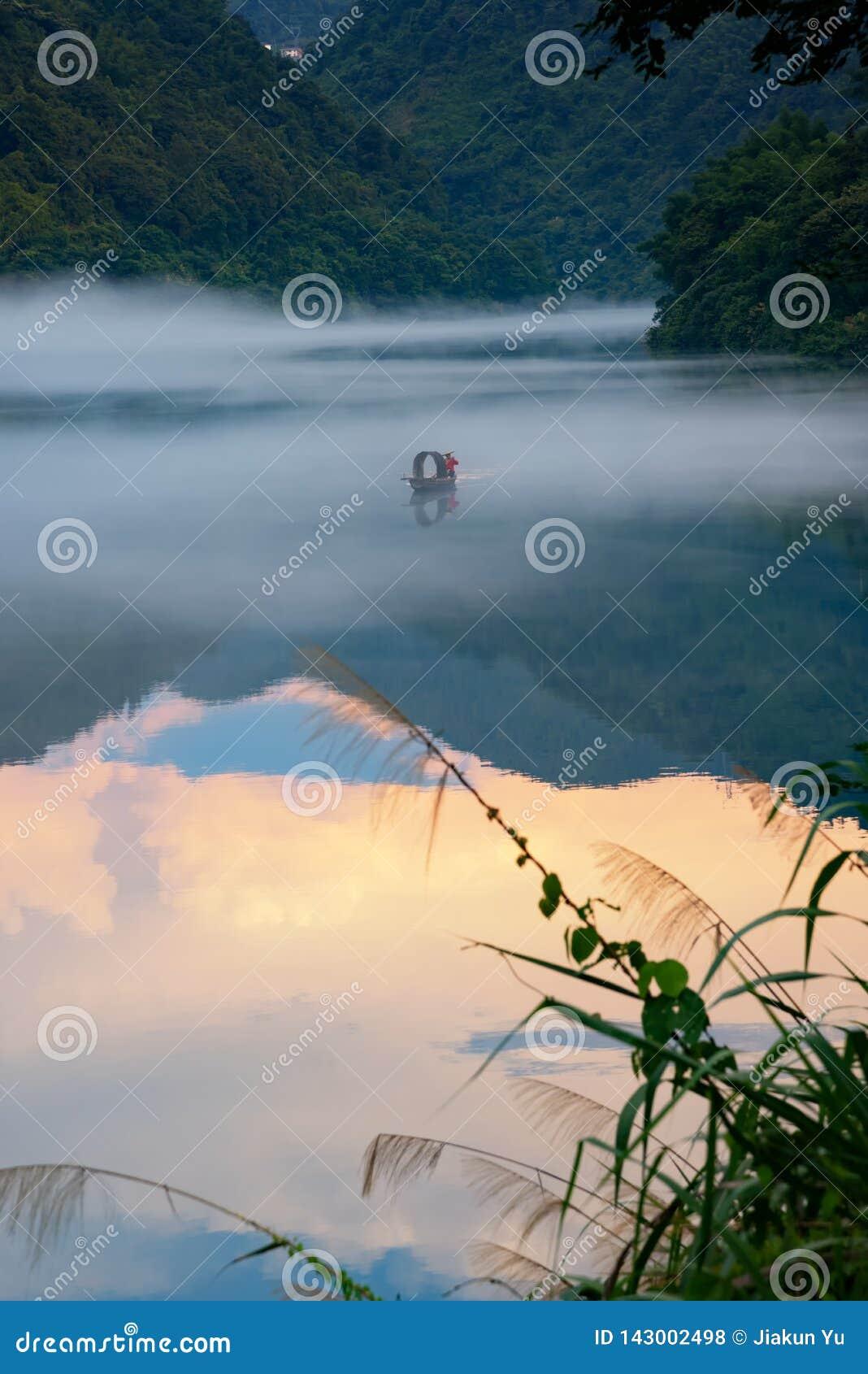 Un fishman en el barco en la niebla en el río, la reflexión de oro de la nube en la superficie del agua
