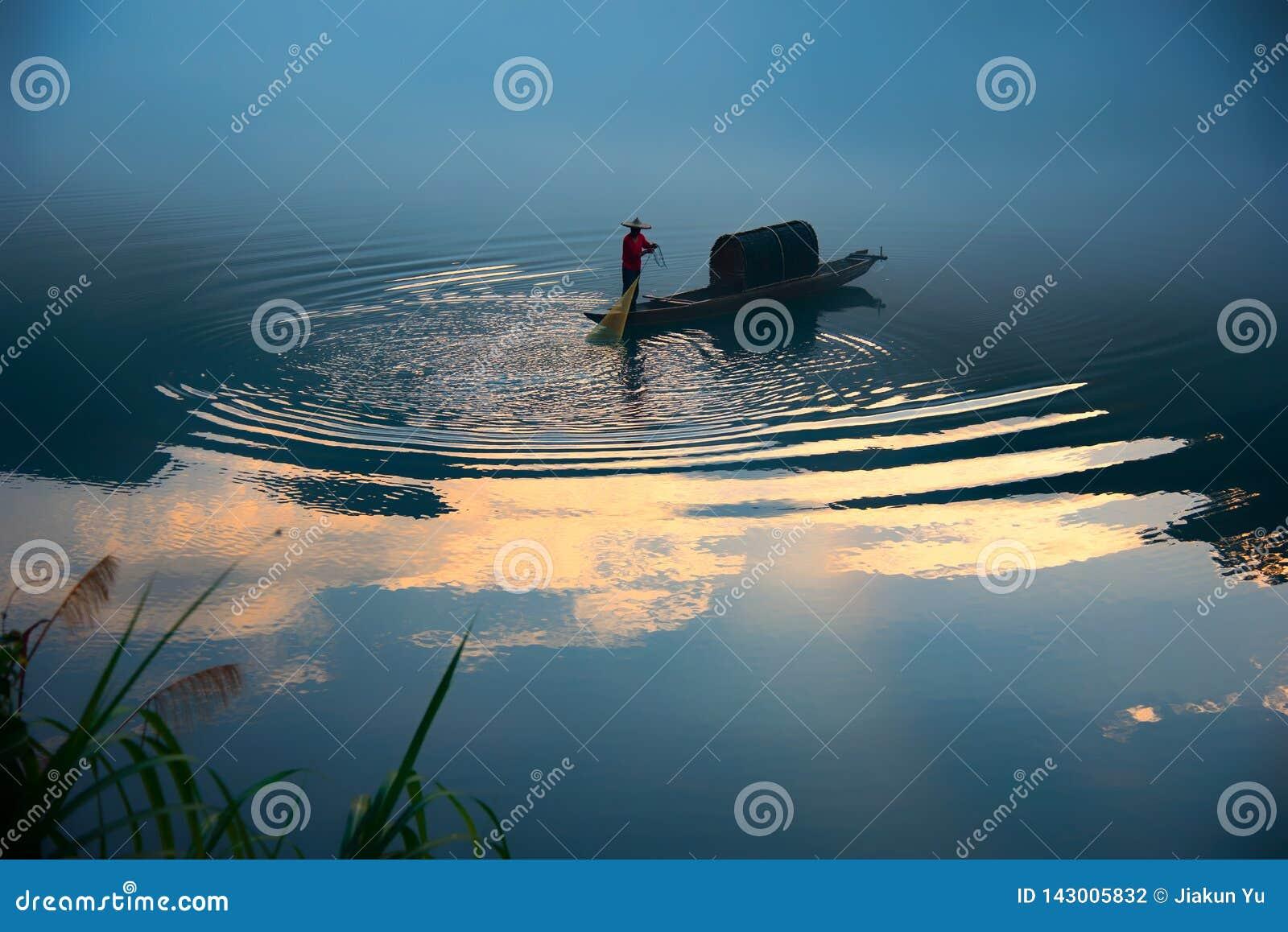 Un fishman sur le bateau dans le brouillard sur la rivière, la réflexion d or de nuage sur la surface de la rivière, ondulation d