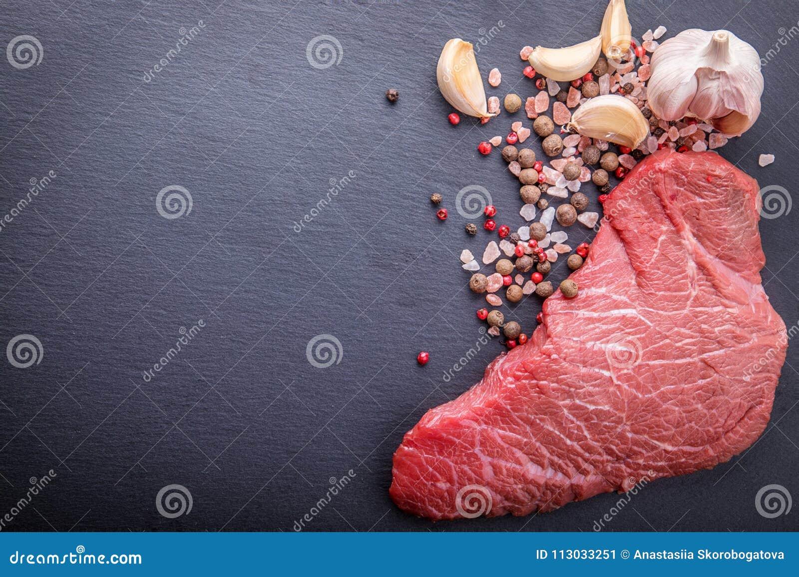 Un fondo con un pedazo crudo de carne de vaca y de verduras, un proceso