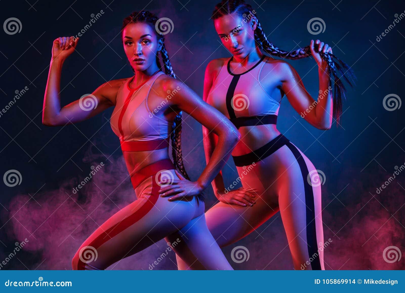Un forte atletico, donne sul fondo di colore che dura negli abiti sportivi di modo, forma fisica e motivazione di sport
