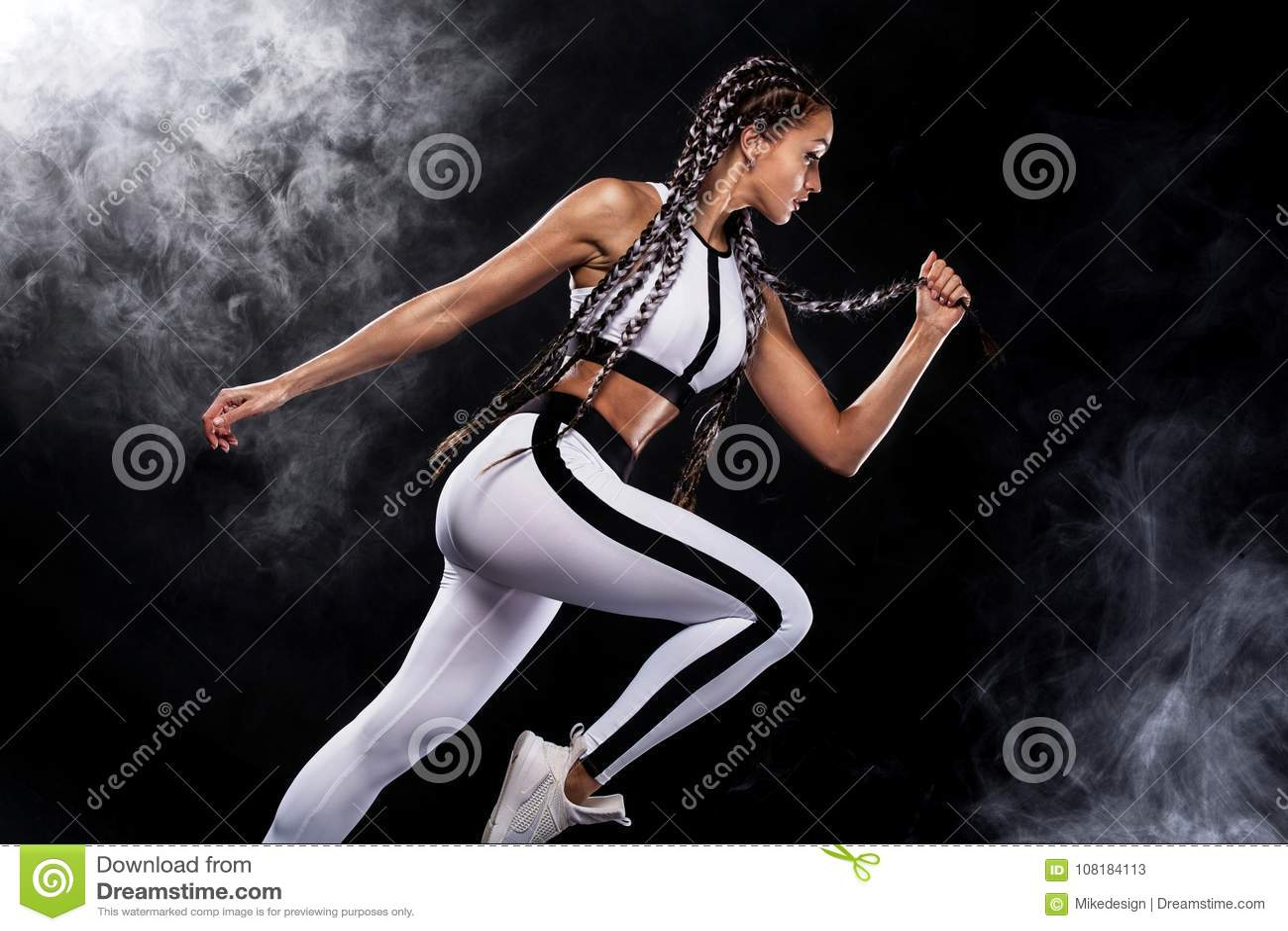 Un forte sprinter della donna e atletico, corrente sul fondo nero che dura nella motivazione degli abiti sportivi, di forma fisic