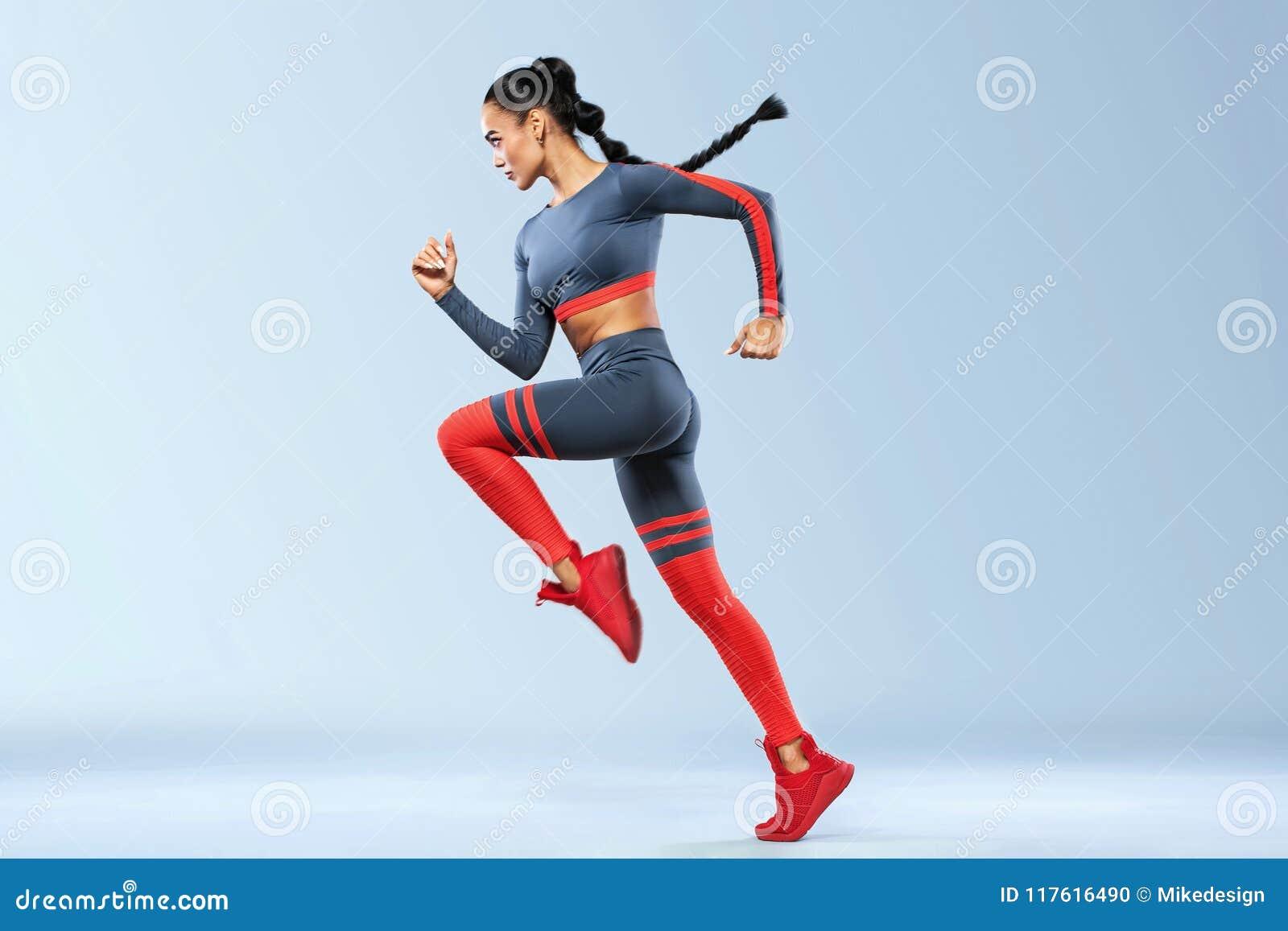 Un forte sprinter delle donne e atletico, eseguente uso nella motivazione degli abiti sportivi, di forma fisica e di sport Concet