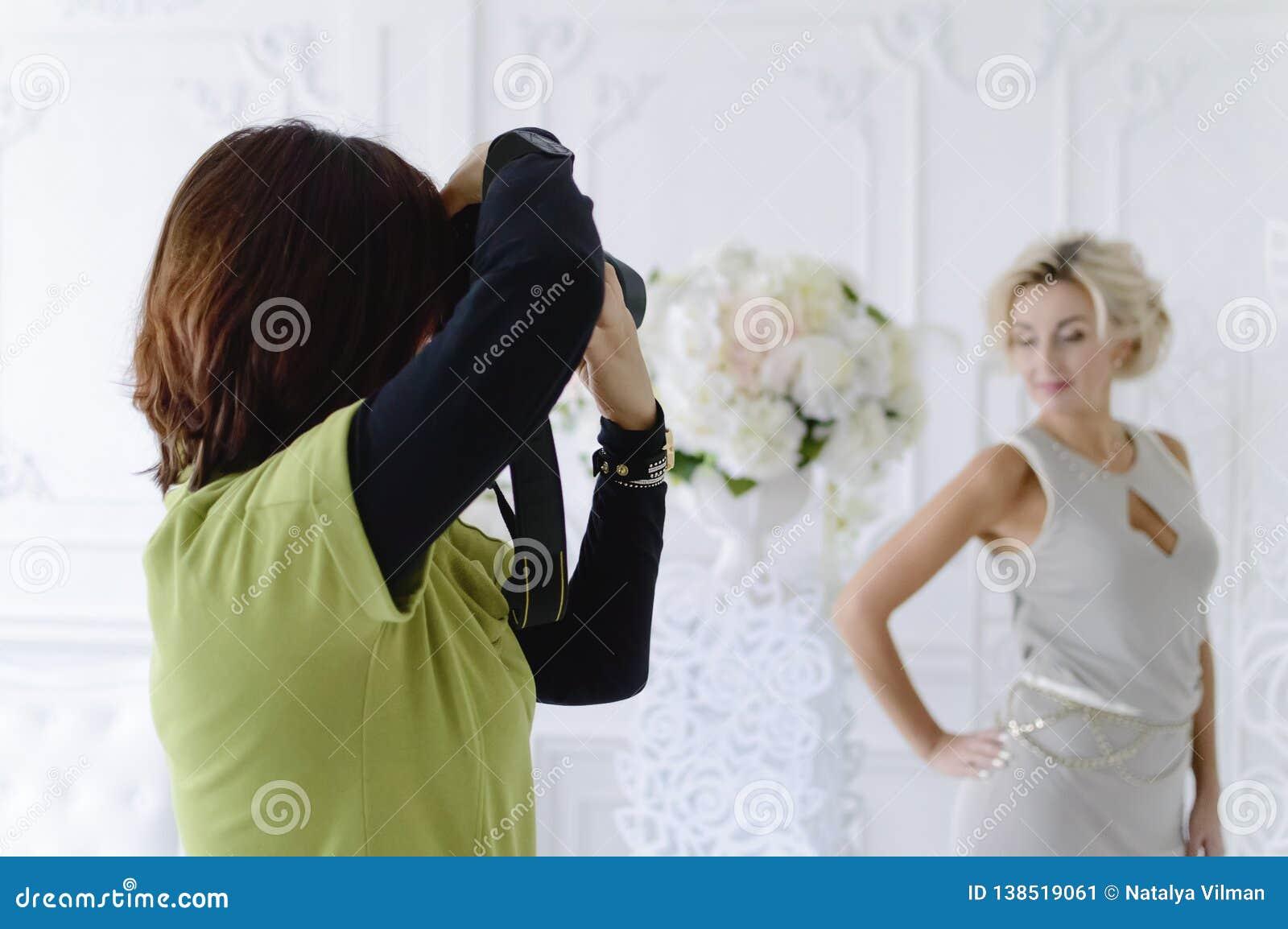 Un fotografo femminile prende un bello modello nello studio