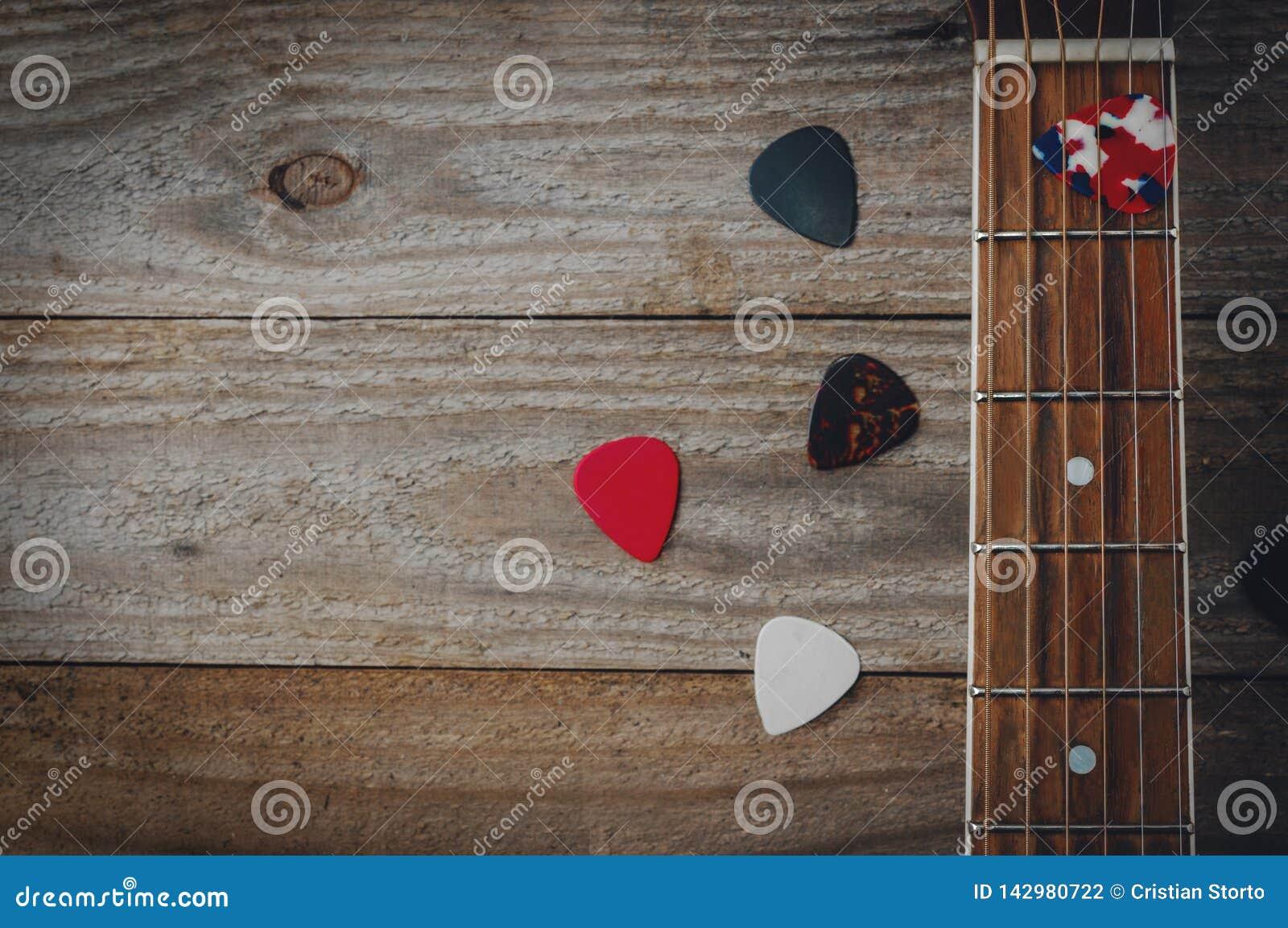 Un fretboard della chitarra acustica ed alcune scelte della chitarra sulla tavola di legno