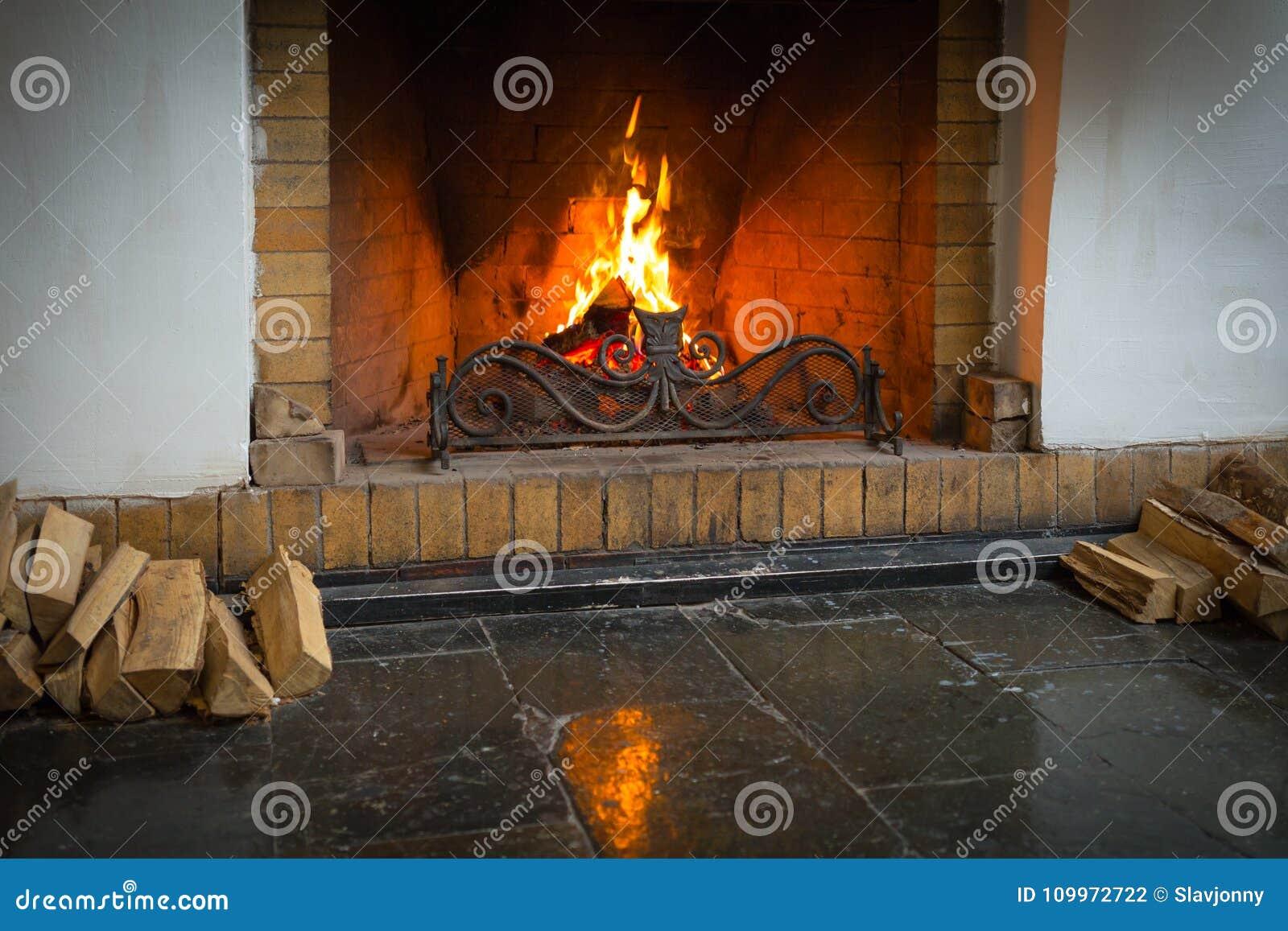 Un fuego del rugido dentro de una piedra grande arqueó la chimenea, con la pila de registros