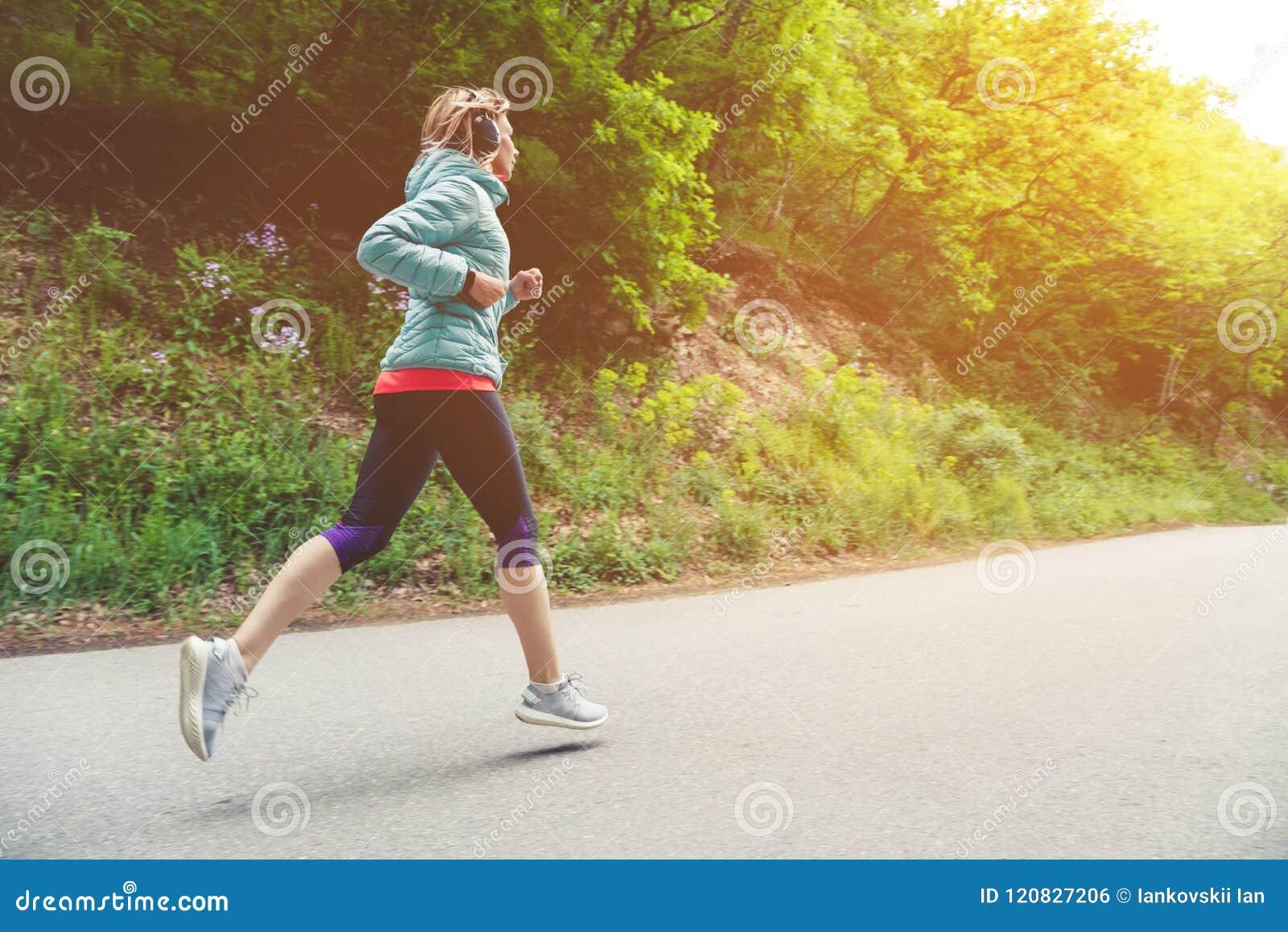 Un funcionamiento rubio joven de la mujer está practicando al aire libre en un parque de la montaña de la ciudad en los rayos cal