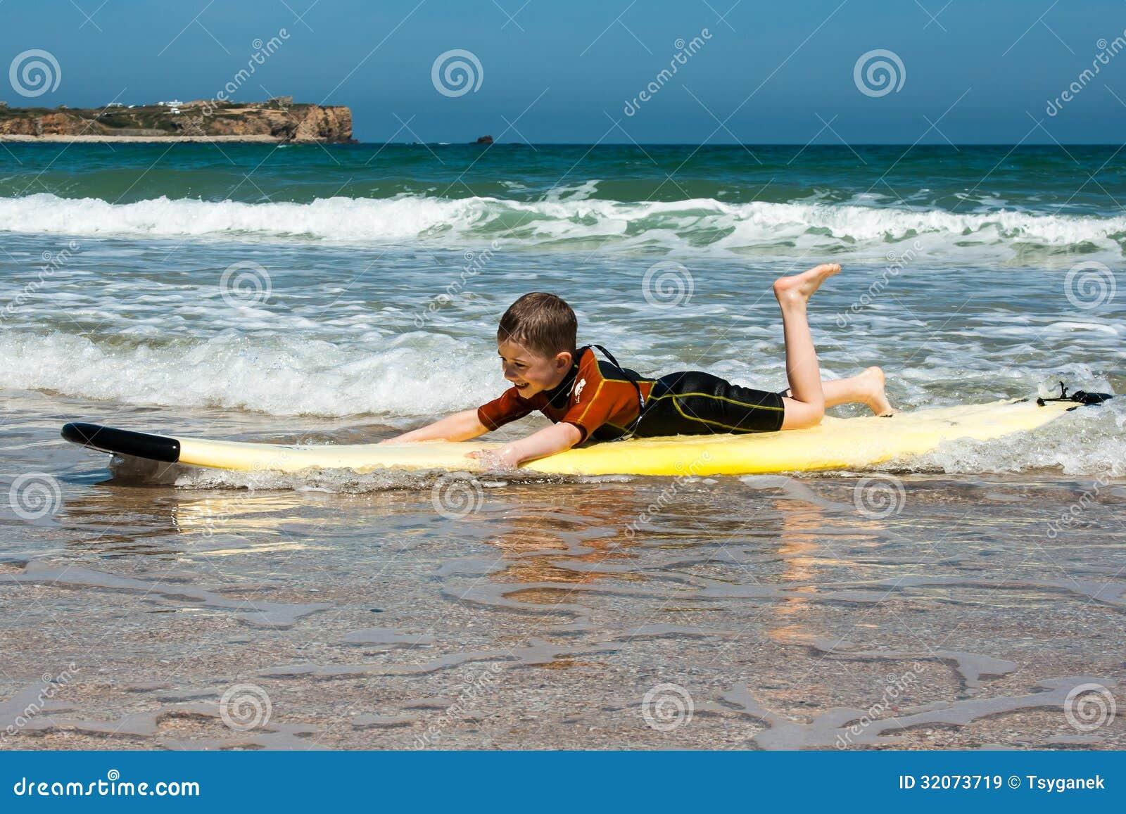 Un garçon apprend à surfer sur un conseil