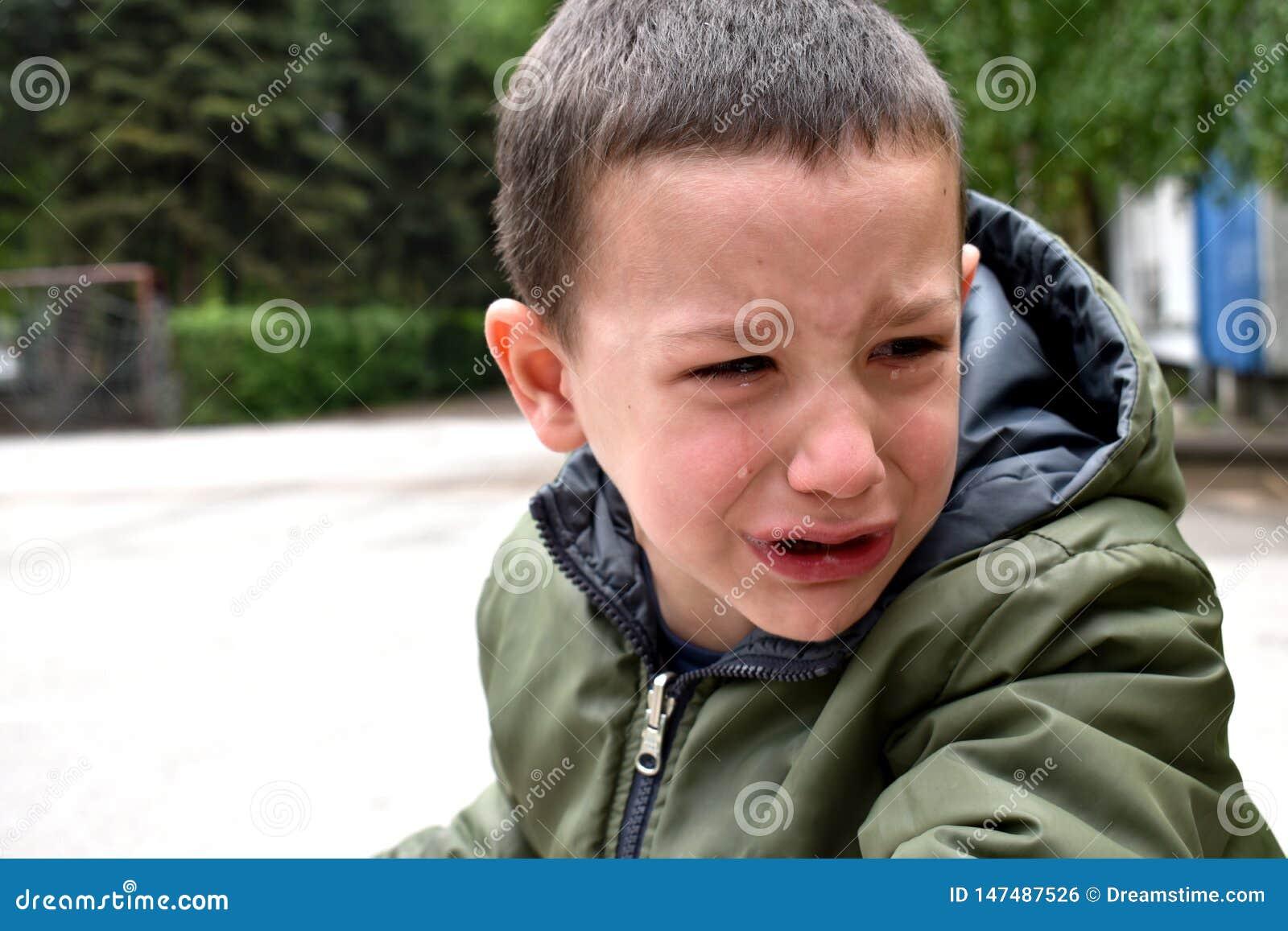 Un garçon bouleversé, avec le visage en larmes en raison des difficultés avec l étude pour monter un vélo