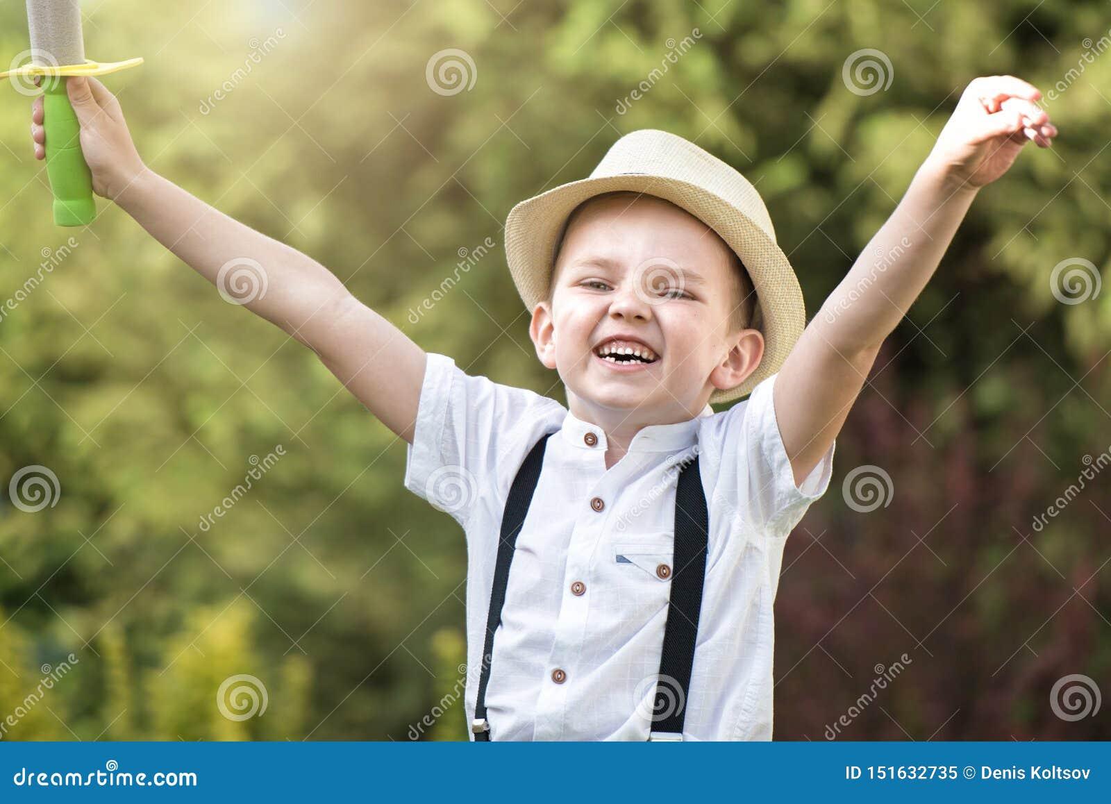 Un garçon dans des promenades et des jeux d un chapeau de paille en parc