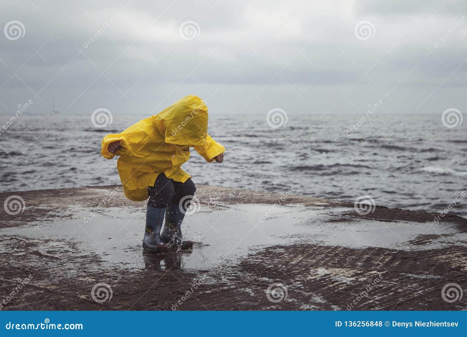 Un garçon dans des sauts jaunes d un imperméable sur des magmas