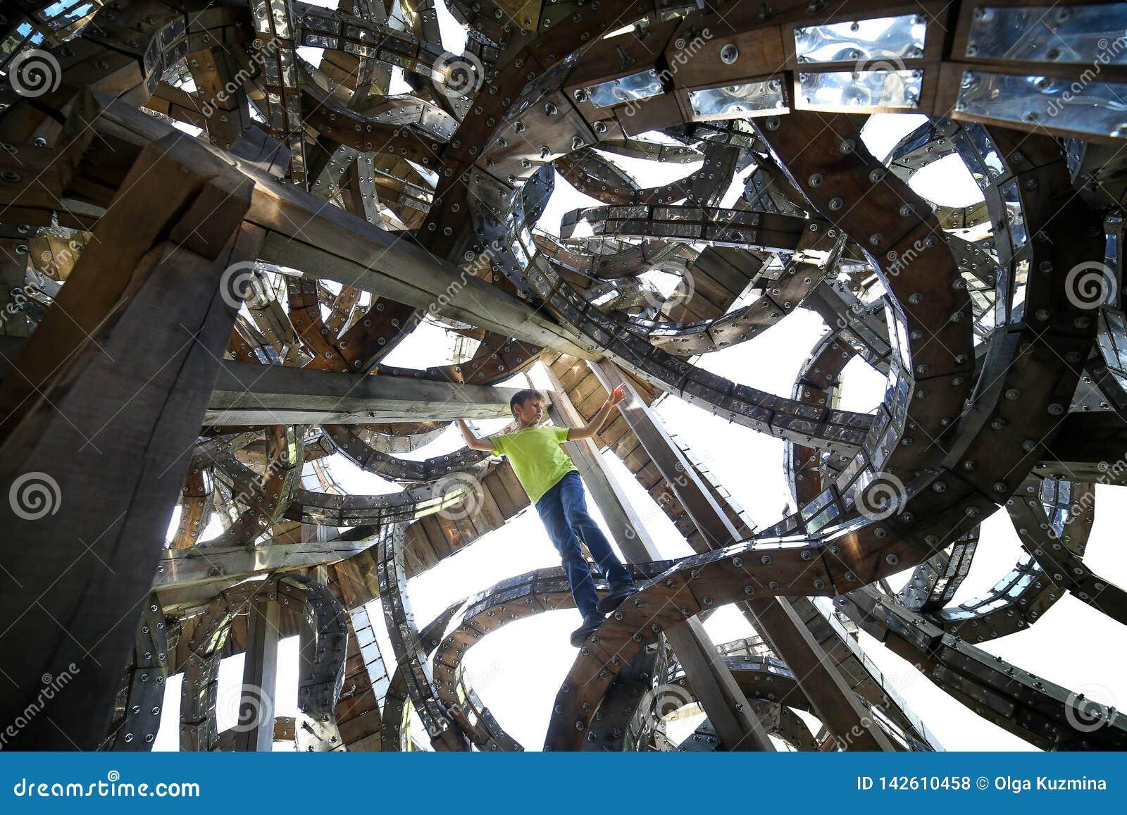 Un gar?on dans une structure architecturale ?trange La construction d art a fait du bois et du m?tal r