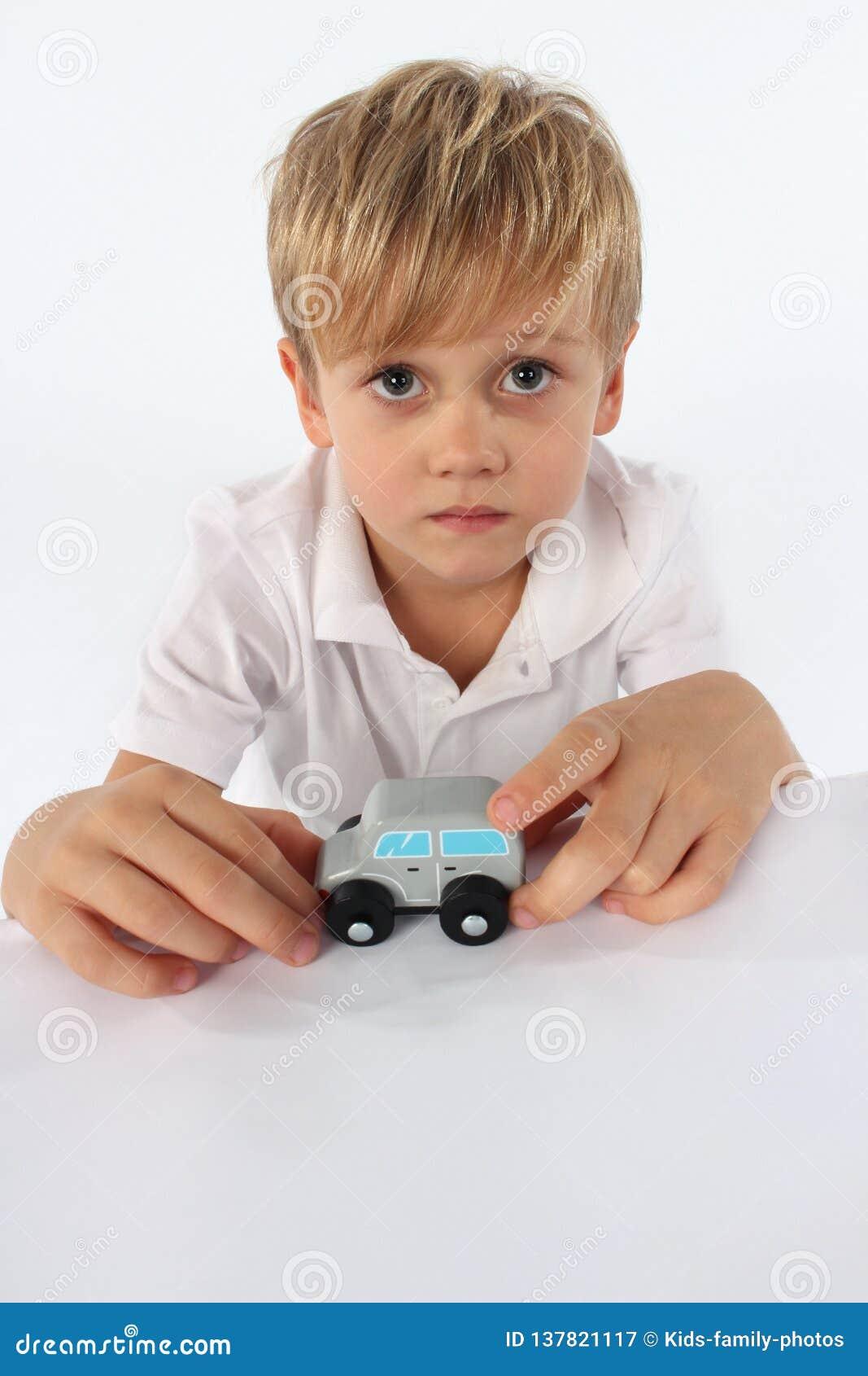 Un garçon de regard angélique d enfant montrant son jouet en bois simple préféré de voiture