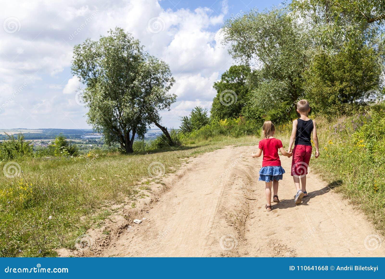 Un garçon et les enfants d une fille marchent sur un chemin de terre un jour ensoleillé d été Badine tenir des mains ensemble tou