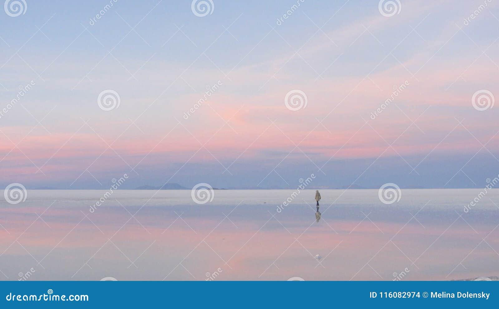 Un garçon marchant pendant le lever de soleil, en Salar de Uyuni, la Bolivie