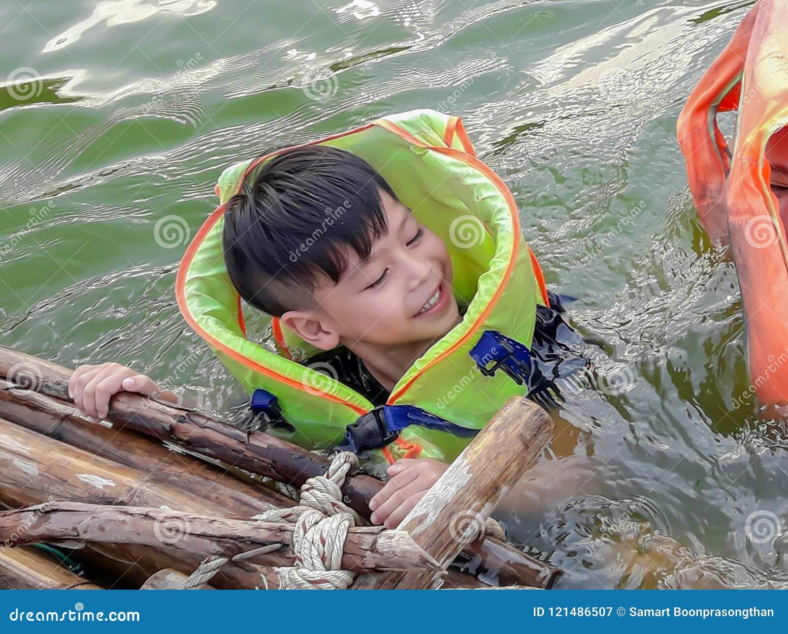 Un garçon utilisant un gilet de sauvetage pour nager sans risque et apprécier